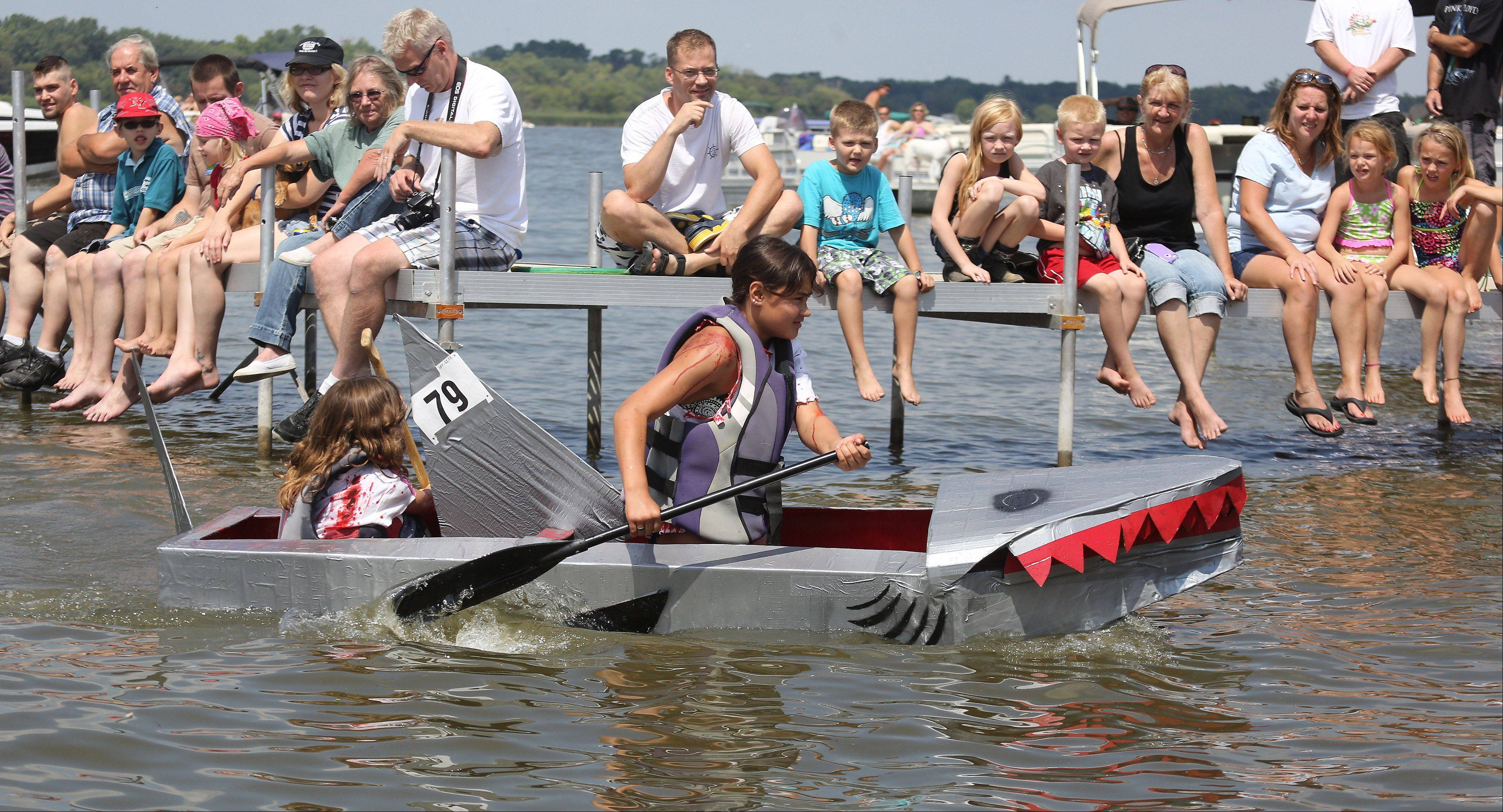 "Spectators watch as sisters Madae and Mya Nieves, of Ingleside, paddle their ""shark'"" boat during the 16th Annual Fox Lake Cardboard Cup Regatta Sunday at Lakefront Park. The race offers medals and trophies to contestants who were limited to making boats out of cardboard, duct tape and paint."