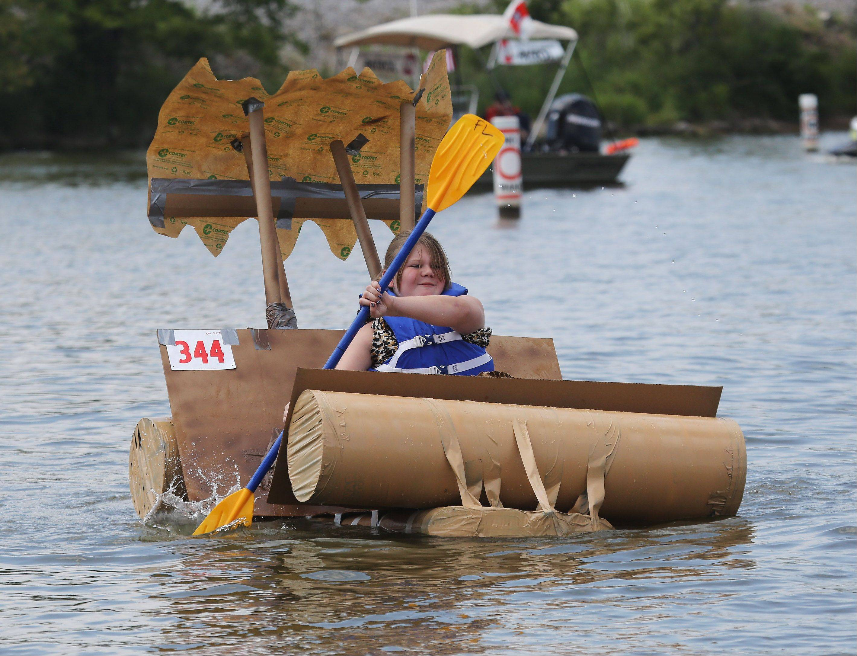 "Haley Masterton paddles her cardboard boat that was made to look like it was a car from the cartoon television show, ""The Flintstones"" during the 16th Annual Fox Lake Cardboard Cup Regatta Sunday at Lakefront Park. The race offers medals and trophies to contestants who were limited to making boats out of cardboard, duct tape and paint."