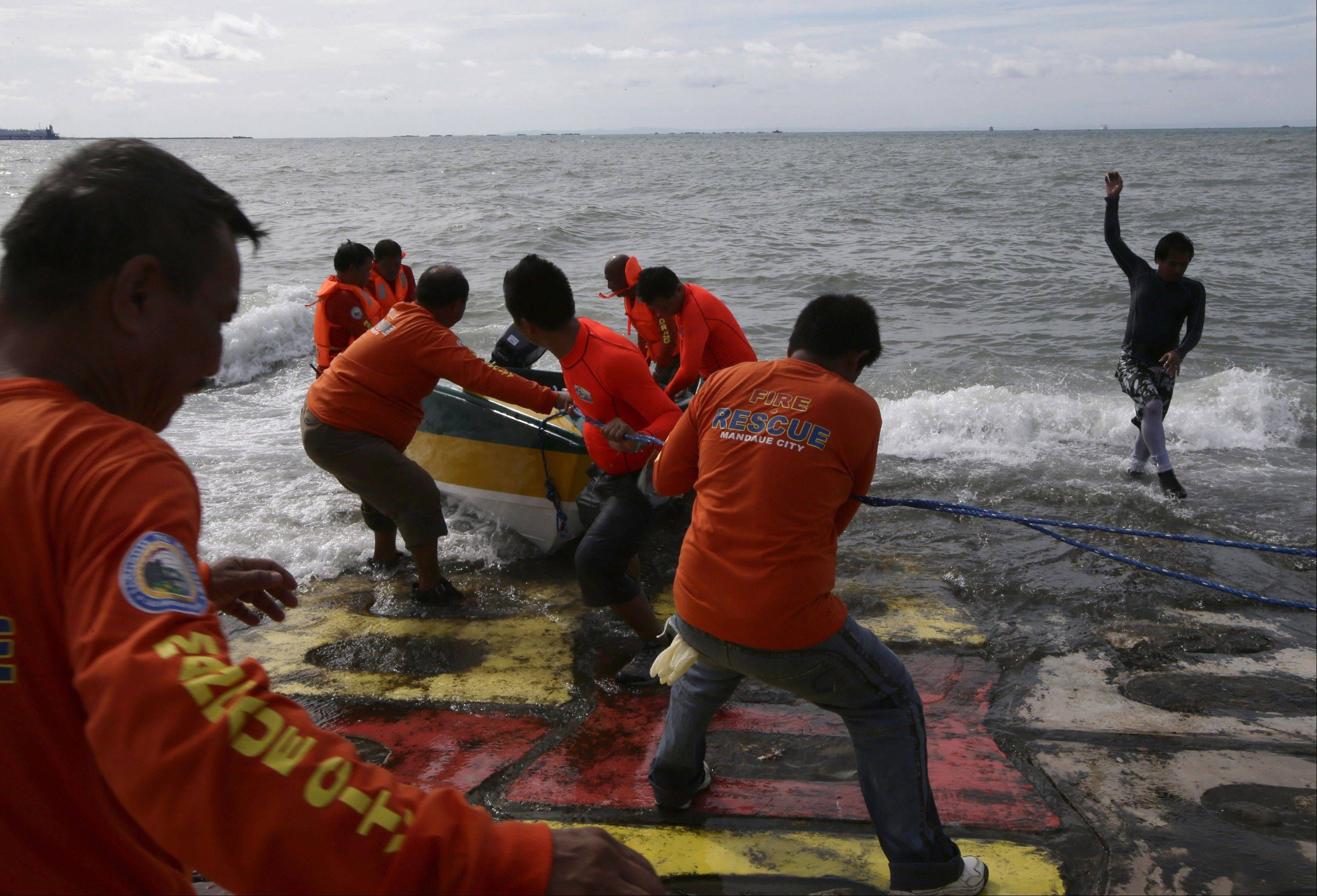 Volunteer divers prepare their rubber to help in the search and rescue operation off Talisay coast, Cebu province Sunday, Aug. 18, 2013 following Friday night's collision of the passenger ferry MV Thomas Aquinas and the cargo ship MV Sulpicio Express Siete in central Philippines.