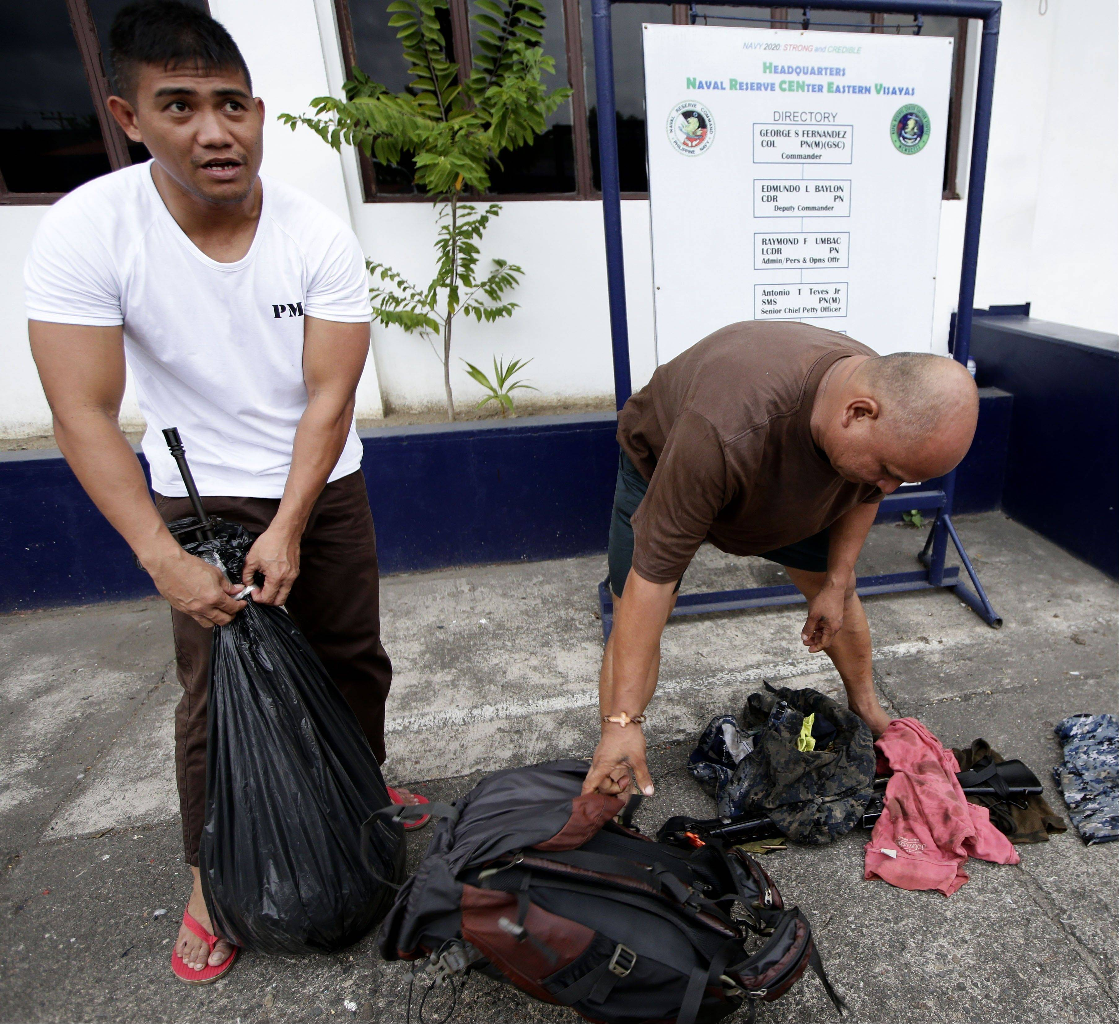 Navy marshal Richard Pestillos, left, of the Philippine Navy and Joseph Austria of the Philippine Coast Guard, show their M-16 rifles and other items they saved as they recount to the Associated Press Sunday Aug.18, 2013 in Cebu city, central Philippines how they saved the lives of about two dozen passengers of the ill-fated MV Thomas Aquinas when it collided with the cargo ship Sulpicio Express Siete off the coast of Talisay near Cebu Friday.