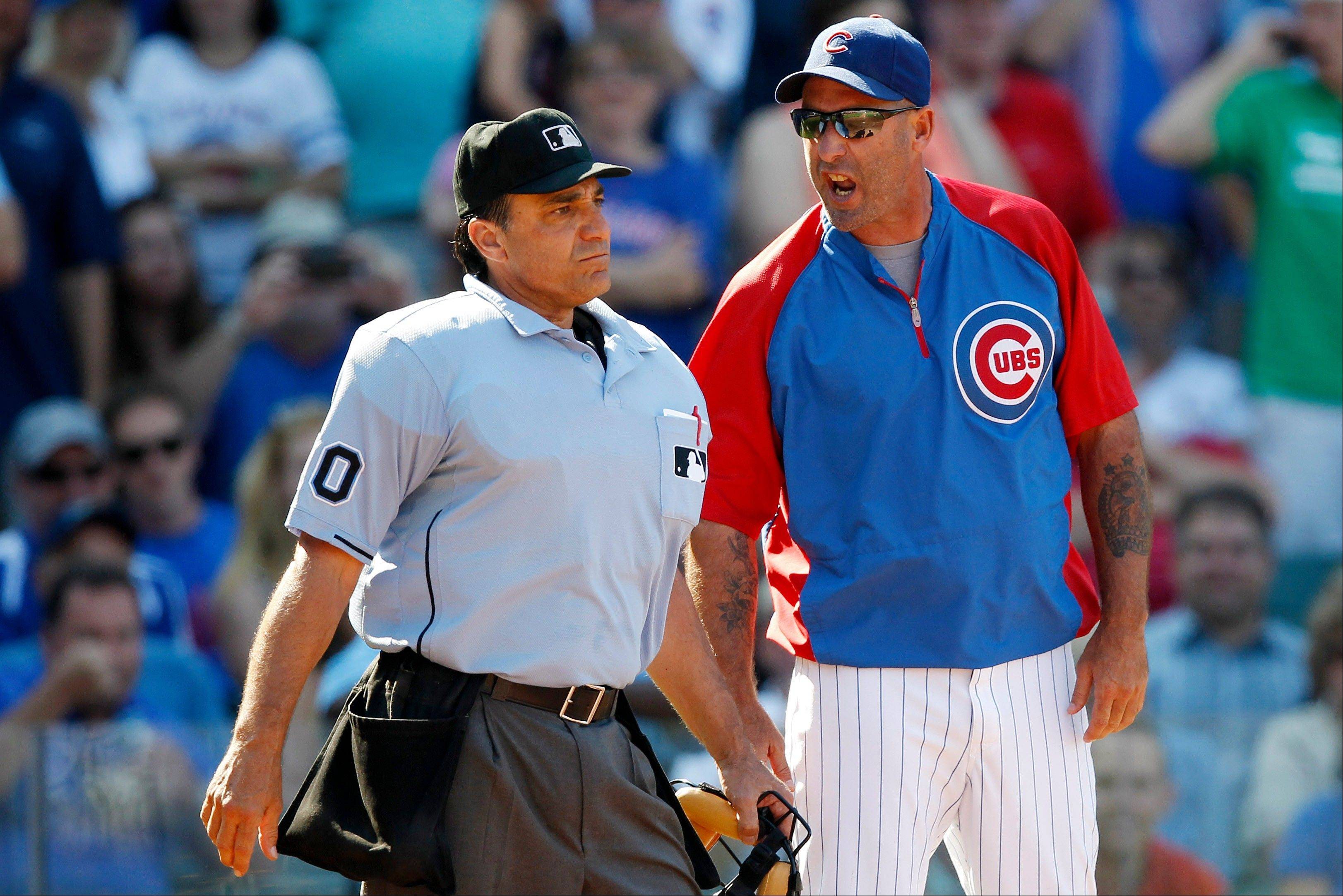 Home plate umpire Phil Cuzzi, left, and Chicago Cubs manager Dale Sveum argue after Cubs' Donnie Murphy was called out on a checked swing during the seventh inning of a baseball game against the St. Louis Cardinals, Sunday, Aug. 18, 2013, in Chicago.