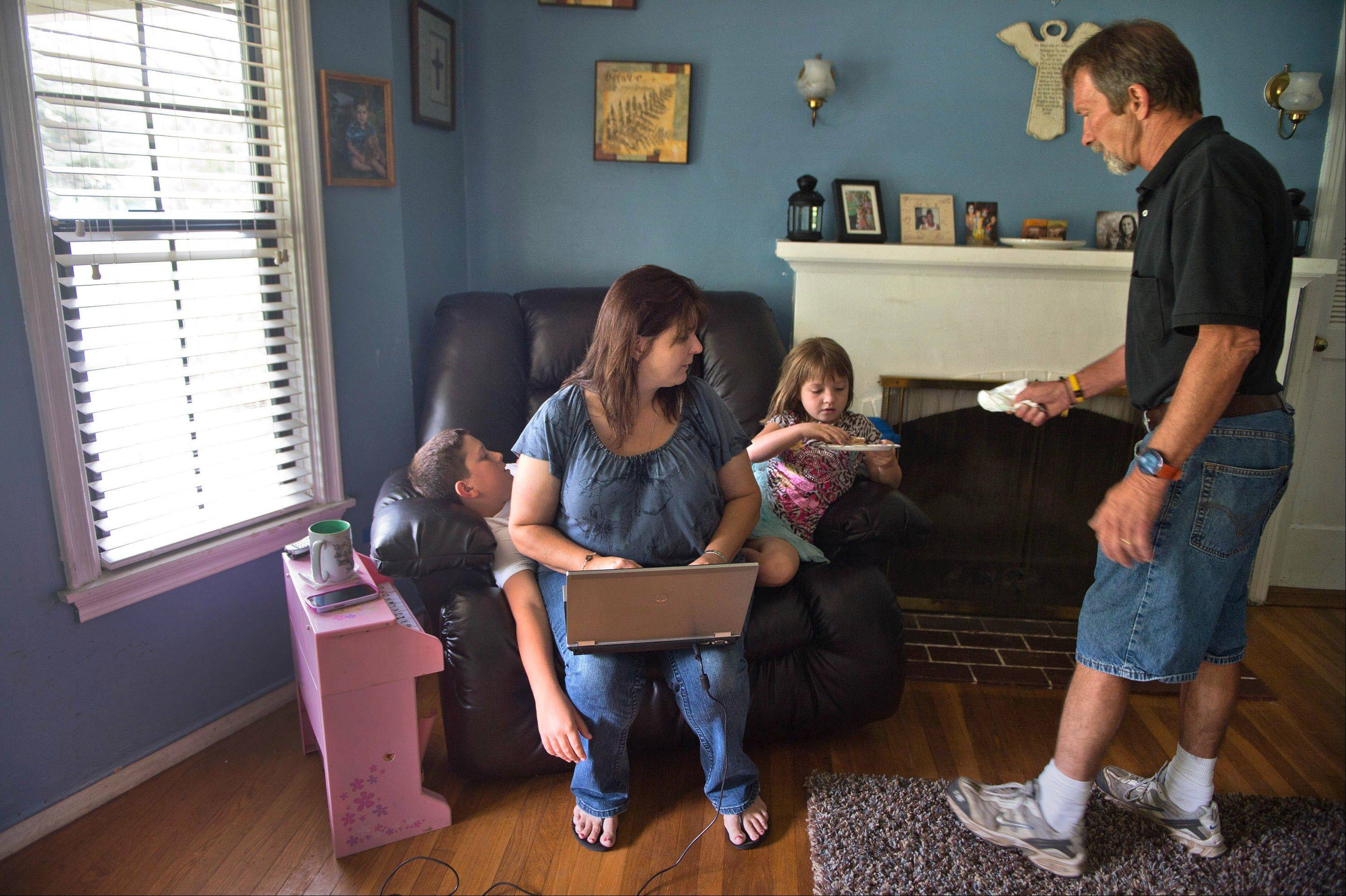 Claire Schooley, center, works from home as she helps husband David Schooley balance life between Alzheimer's disease and caring for their children, Nathaniel, 12, and Hannah, 6.