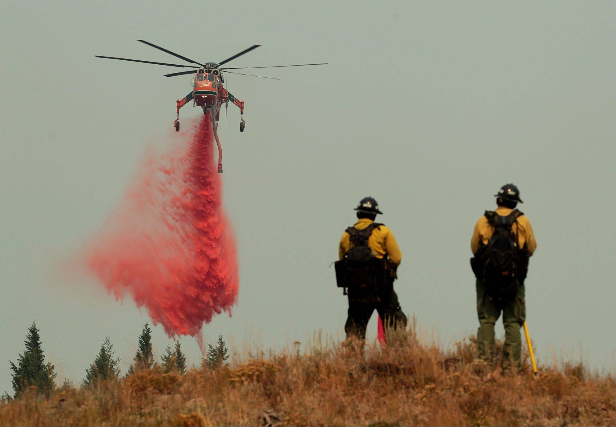 A helicopter makes a drop on a dozer line around a home to protect it from the Beaver Creek Fire on Sunday outside of Ketchum, Idaho.