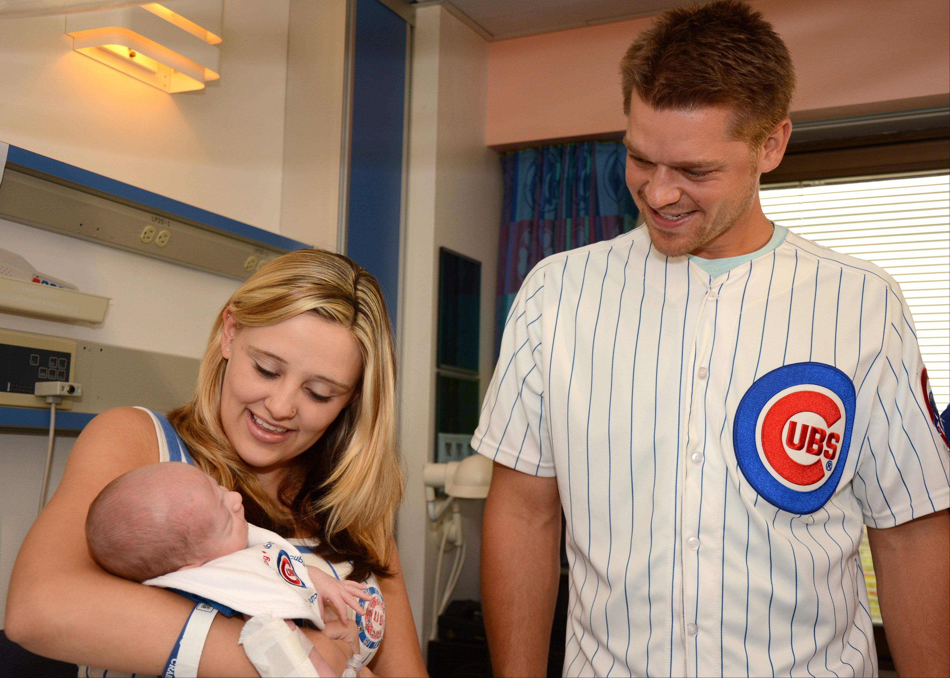 Brook Aguilar holds up her 4-week-old son RyLee Cash Capra to meet Chicago Cubs pitcher Michael Bowden on Monday during his visit to Advocate Children�s Hospital in Park Ridge. Aguilar said she rushed home Sunday night after learning of the visit to get the family�s Cubs gear.
