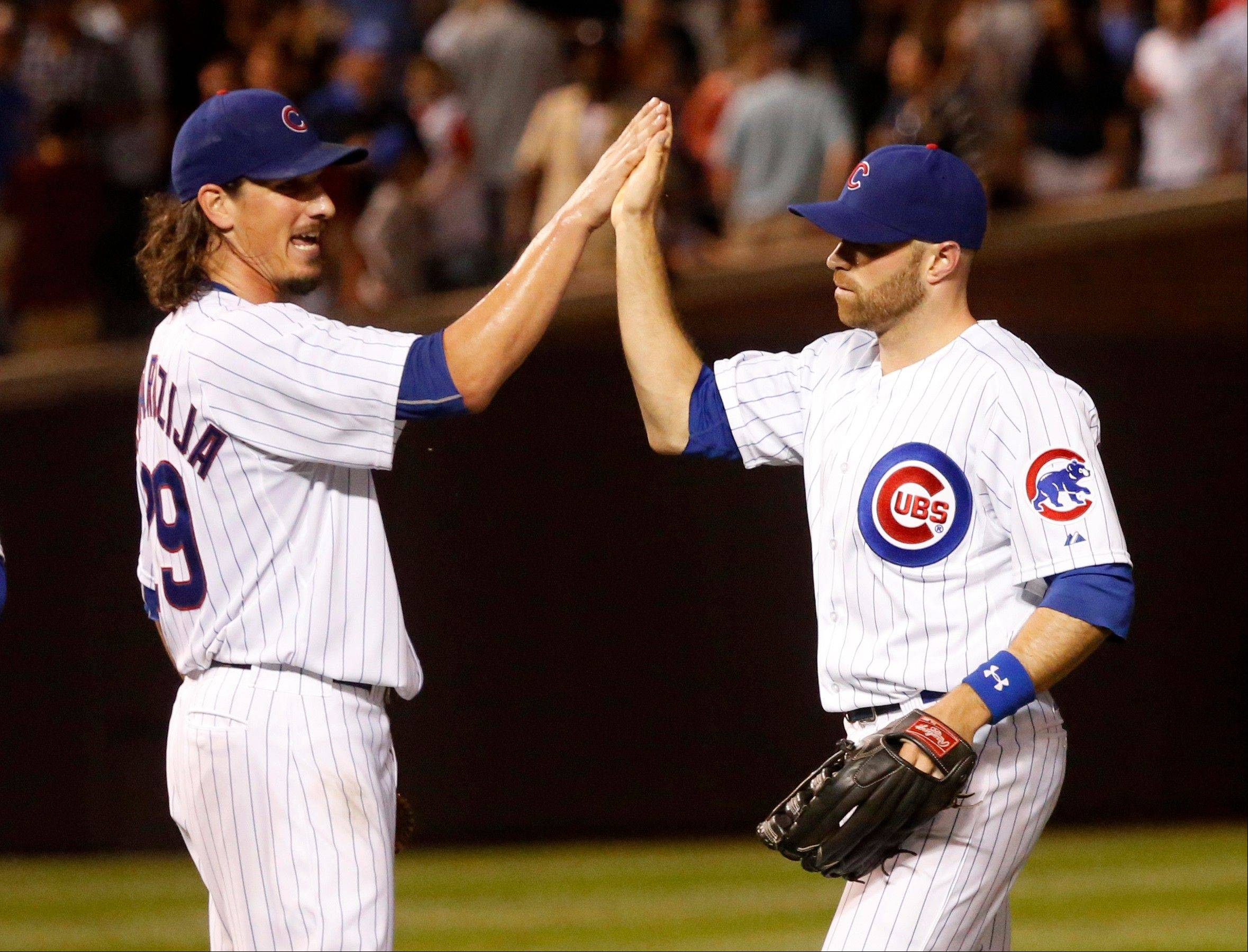 Starting pitcher Jeff Samardzija, left, celebrates with right fielder Nate Schierholtz after the Cubs' victory over the Nationals on Monday night at Wrigley Field. Samardzija went the distance for the win, and Schierholtz hit for distance with 2 home runs and 6 RBI.