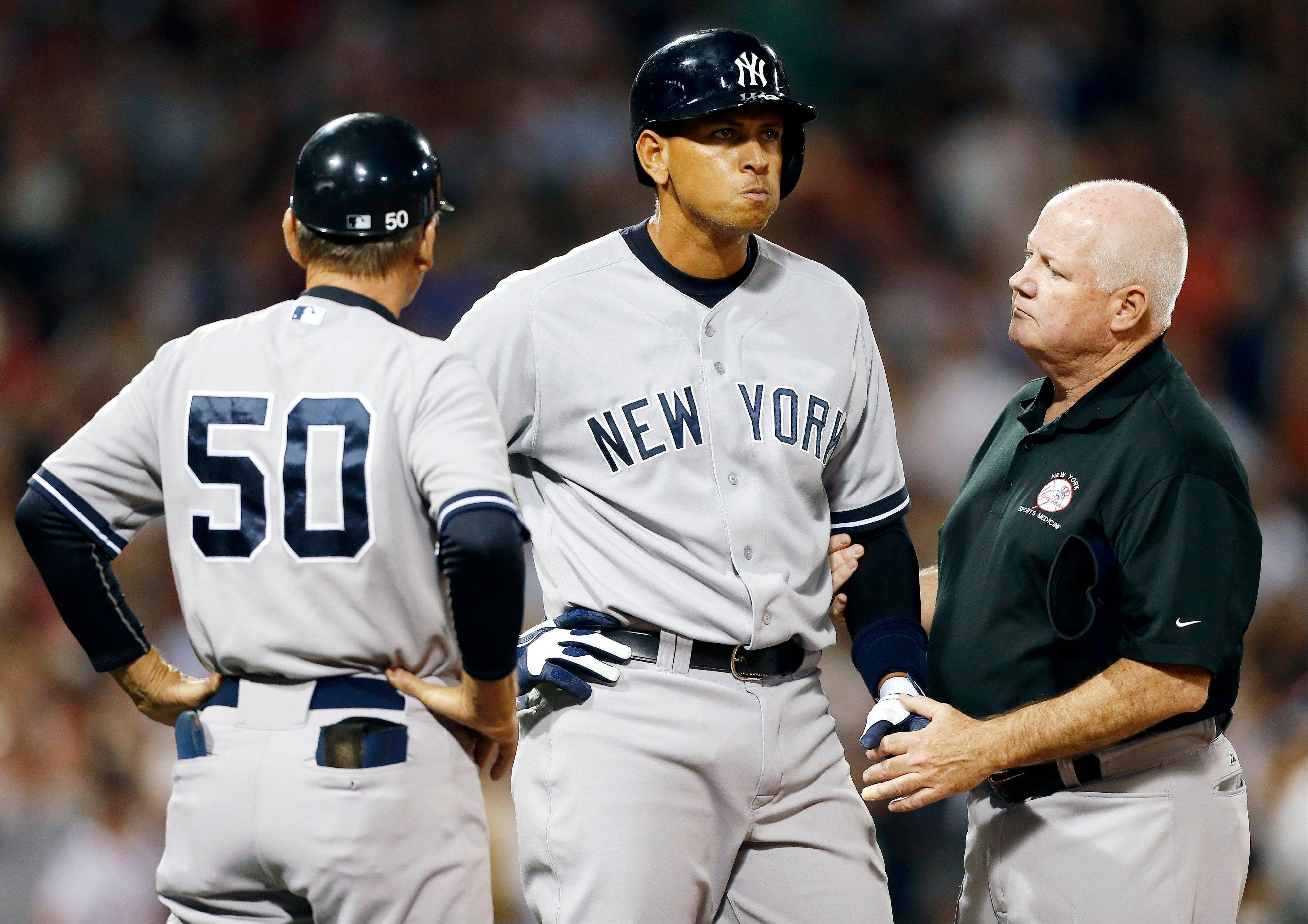 Alex Rodriguez, center, is tended to by a trainer at first base after being hit by a pitch from Red Sox pitcher Ryan Dempster in the second inning of Sunday�s game in Boston.