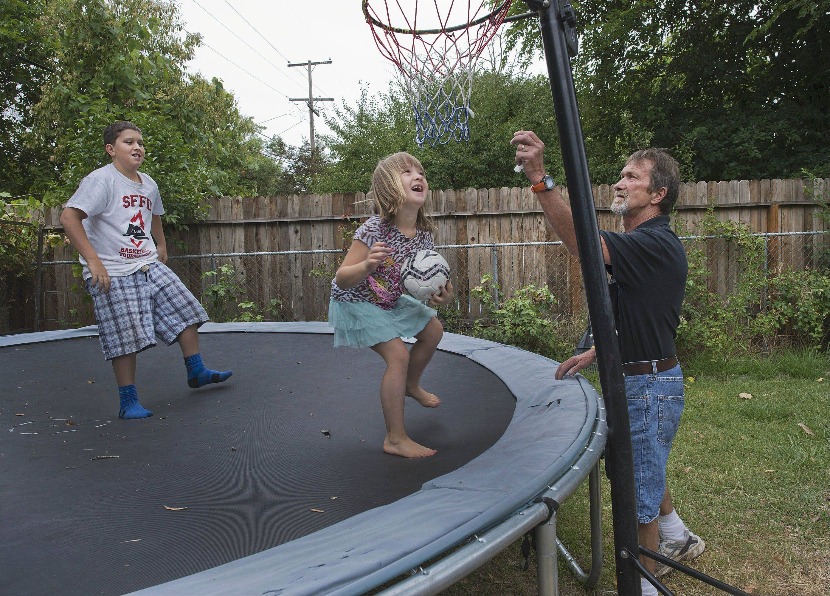 David Schooley, right, keeps a close eye on his children, Nathaniel, 12, and Hannah, 6, in their backyard.