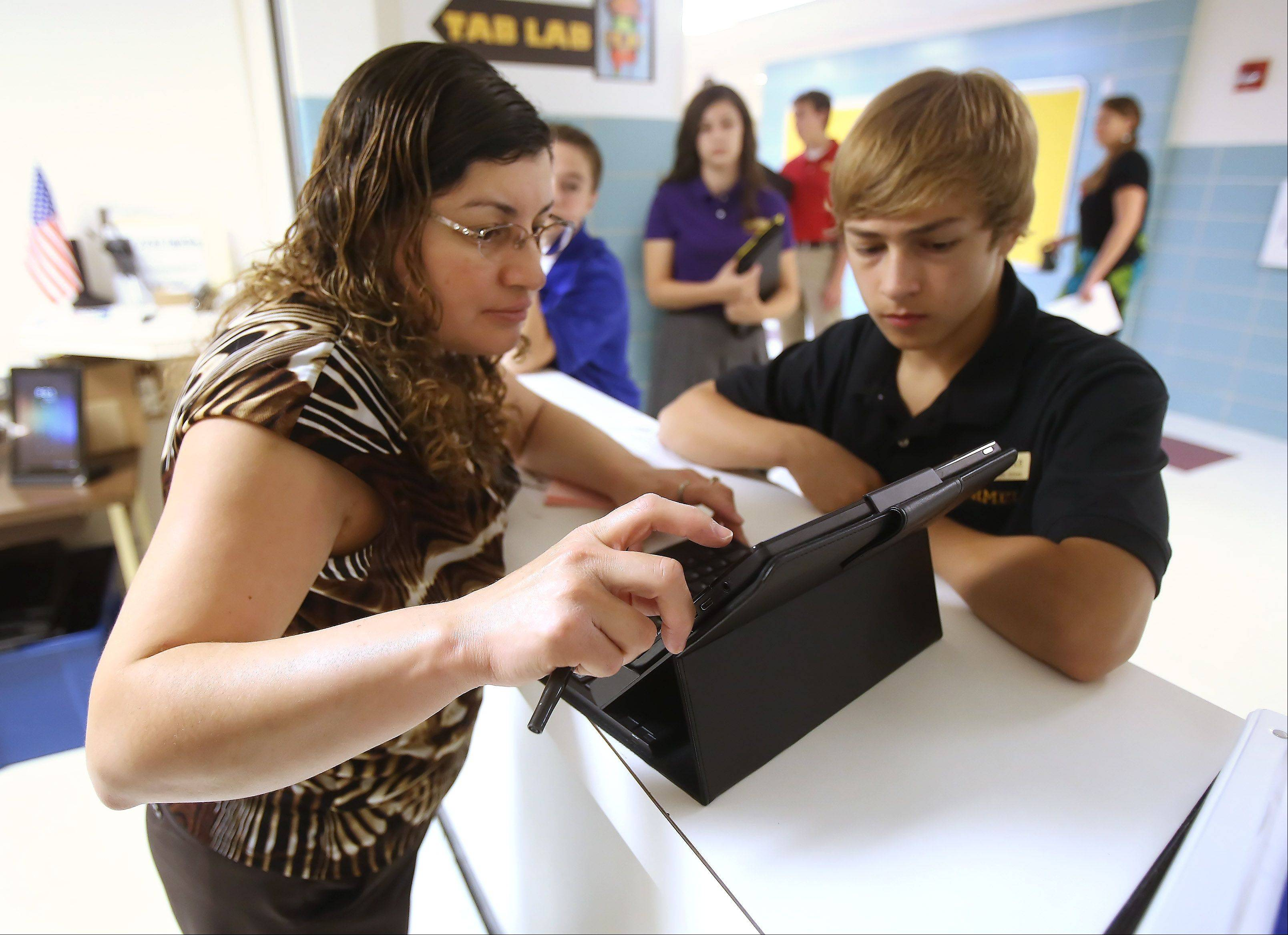 Carmel Catholic High School Tab Lab assistant Catalina Guadarrama helps Michael Tortorice with his computer tablet problem during the first day of classes Monday at the Mundelein school. Every Carmel student is given a tablet to work on during the year.