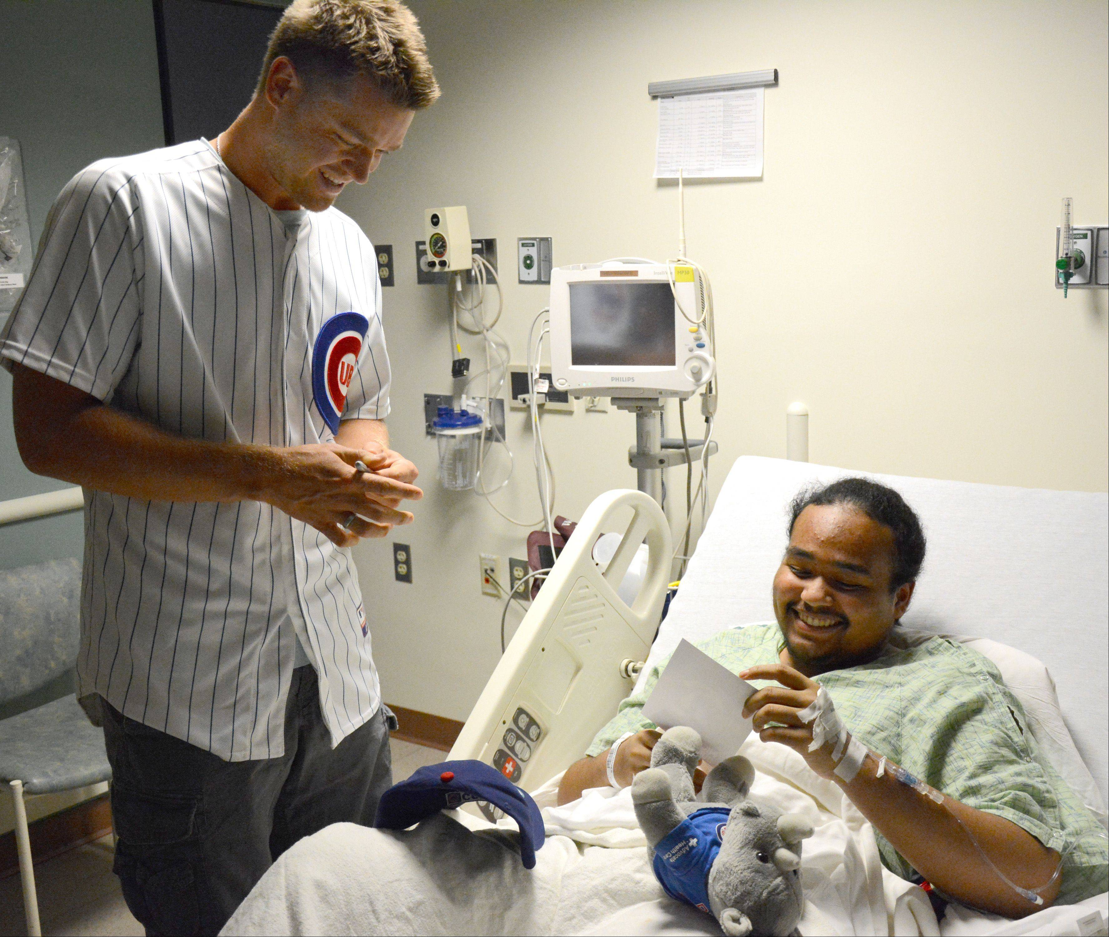 Chicago Cub Michael Bowden hands an autographed picture to Gerek Wright, of Maywood, during a visit Monday to Advocate Children's Hospital in Park Ridge. Bowden told Wright that he was leaving his autograph so that Wright wouldn't forget him.