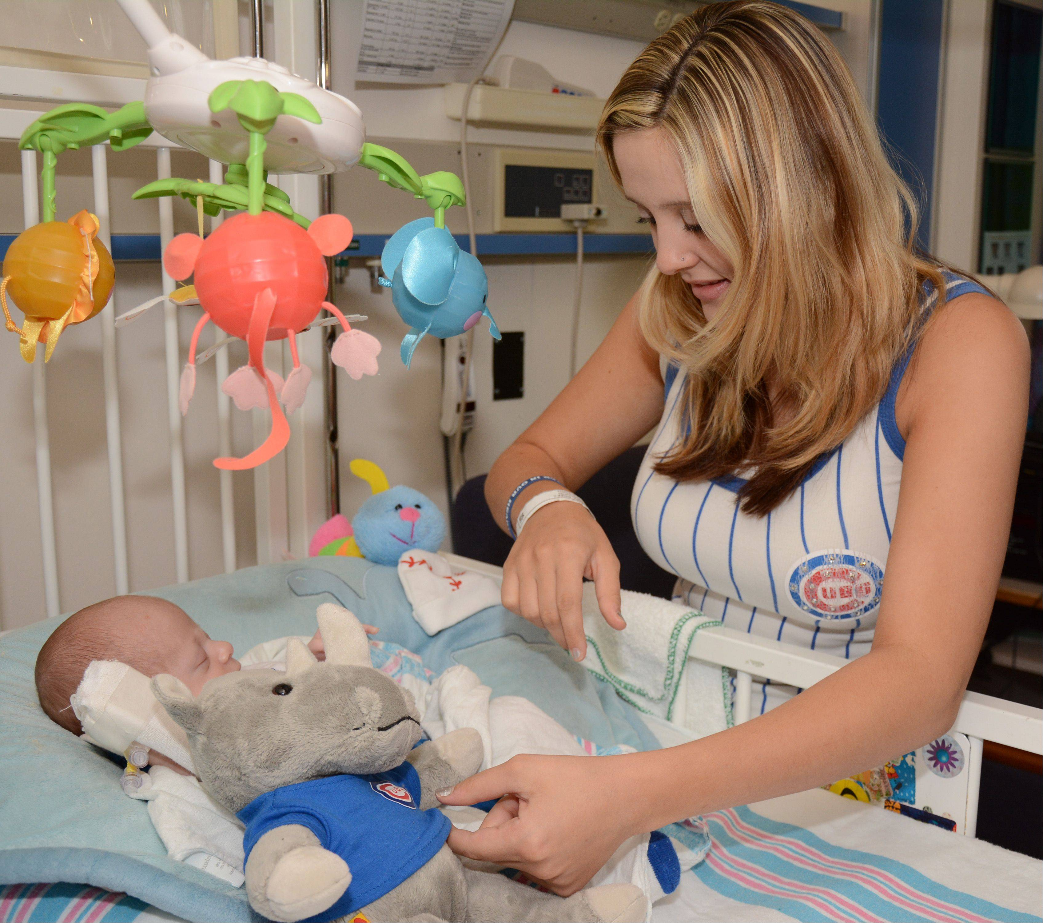 Brook Aguilar tucks a stuffed rhinoceros in with her 4-week-old son RyLee Cash Capra during a visit Monday by Chicago Cubs pitcher Michael Bowden. Capra's father, Ryne, was especially excited by the visit because he was named after former Cub Ryne Sandberg.