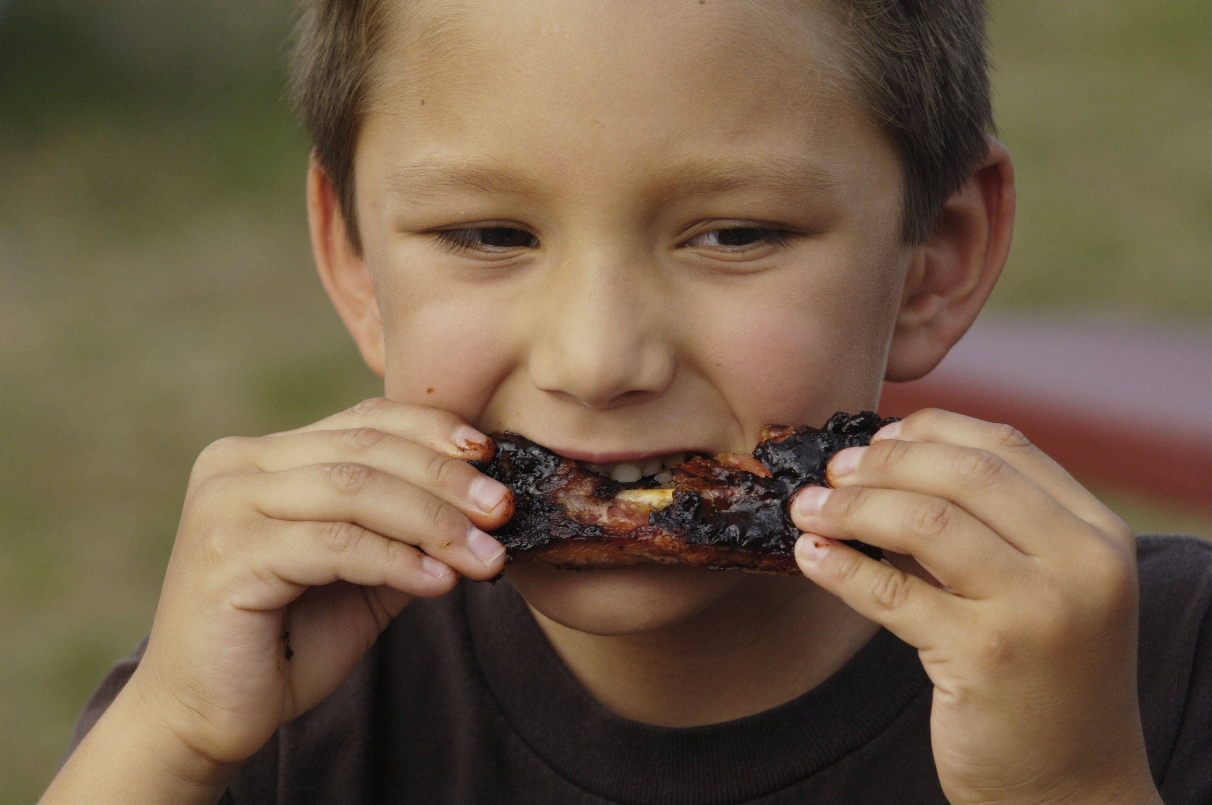 Ribs, like these enjoyed by Adrian Gonzalez, 6, of Gurnee, are the centerpiece of the Vernon Hills Park District's Little Bear Ribfest Aug. 23 and 24 at Century Park.