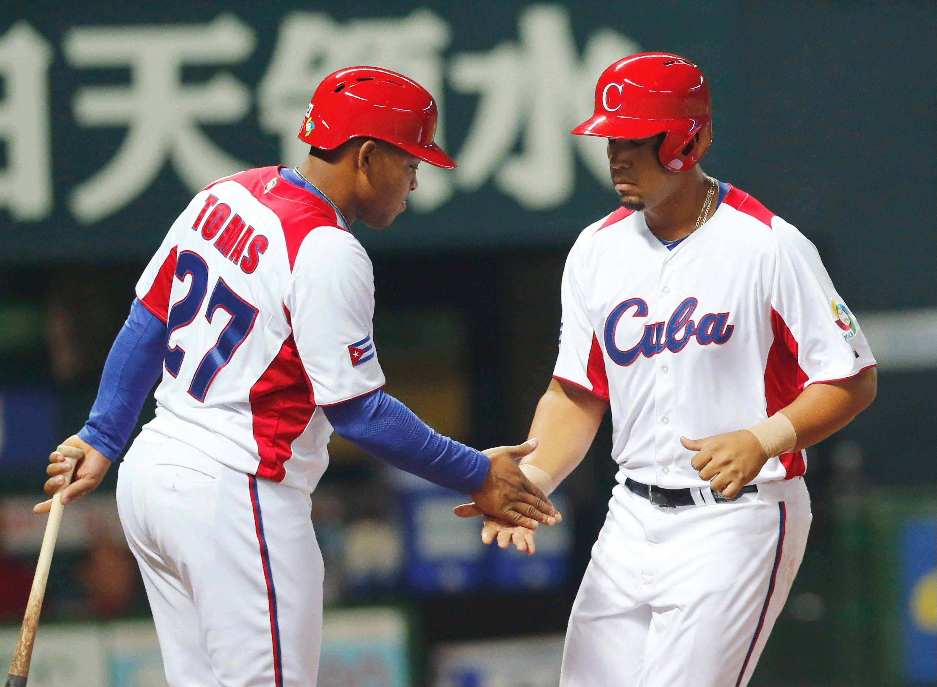 Cuba's first baseman Jose Abreu, right, is celebrated by teammate Tomas Yasman at home after hitting a grand slam off China's Liu Yu in the fifth inning of their World Baseball Classic first round game in Fukuoka, Japan, Monday, March 4, 2013.