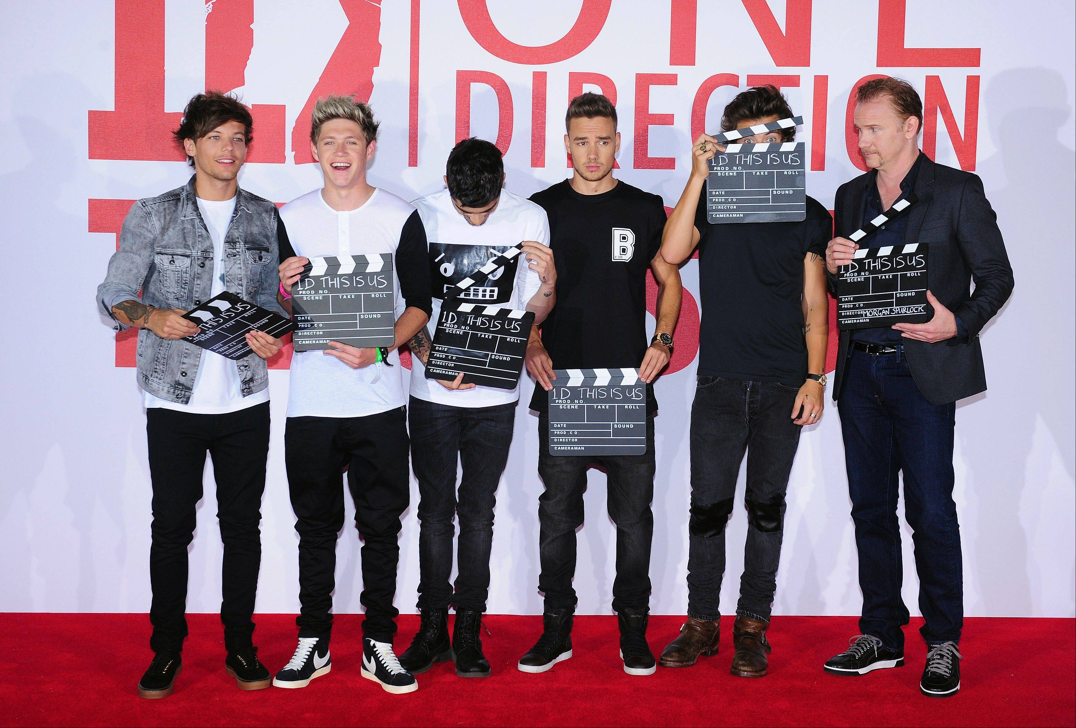 One Direction � Louis Tomlinson, left, Niall Horan, Zayn Malik, Liam Payne and Harry Styles � promote their new film, �This is Us,� with director Morgan Spurlock on Monday in London. The film is an intimate all-access look at life on the road for the global music phenomenon.