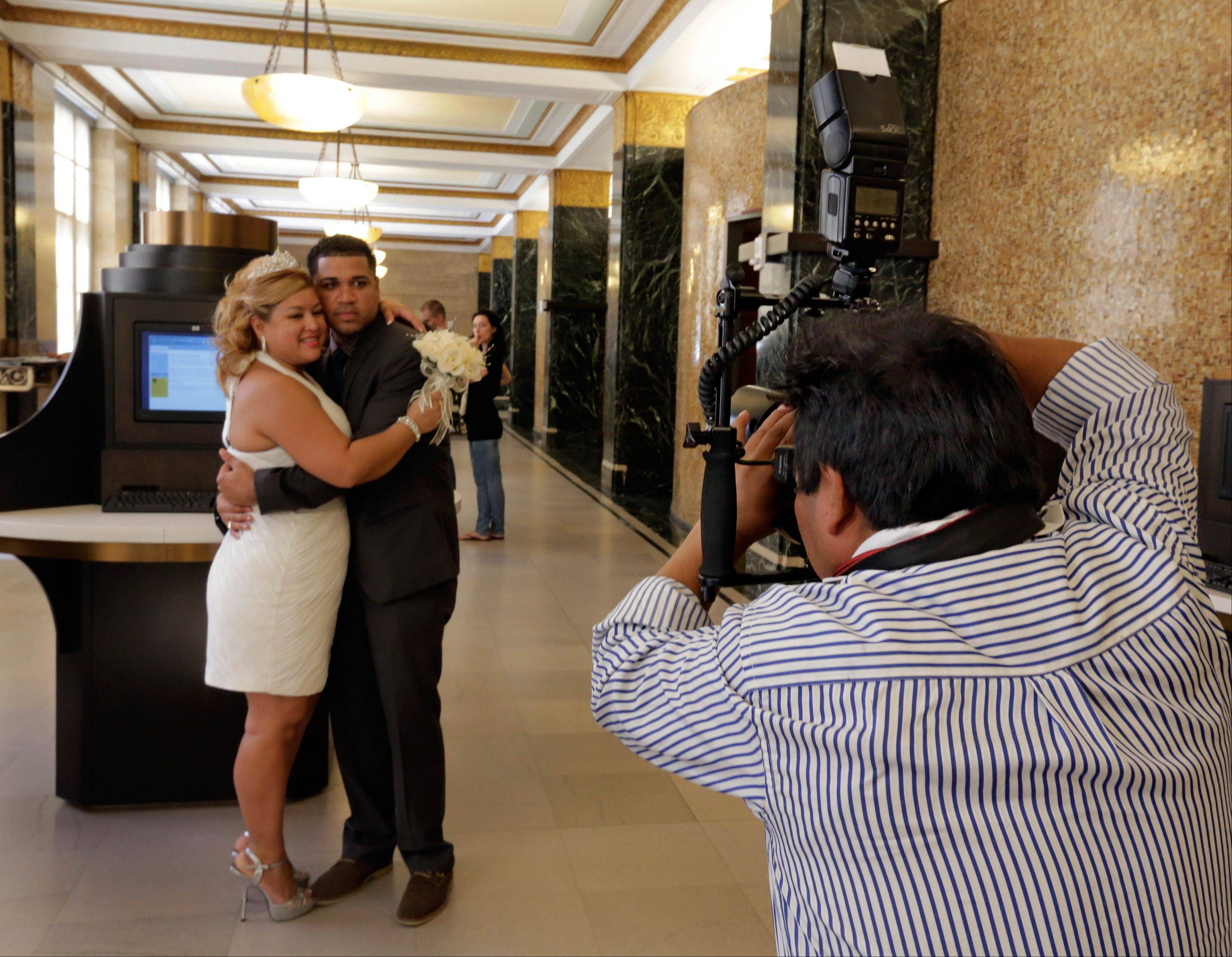 Wedding photographer Braulio Cuenca poses groom Jorge Mejia and bride Irma Aguilar, of the Bronx borough of New York, before their ceremony in New York's Office of the City Clerk.