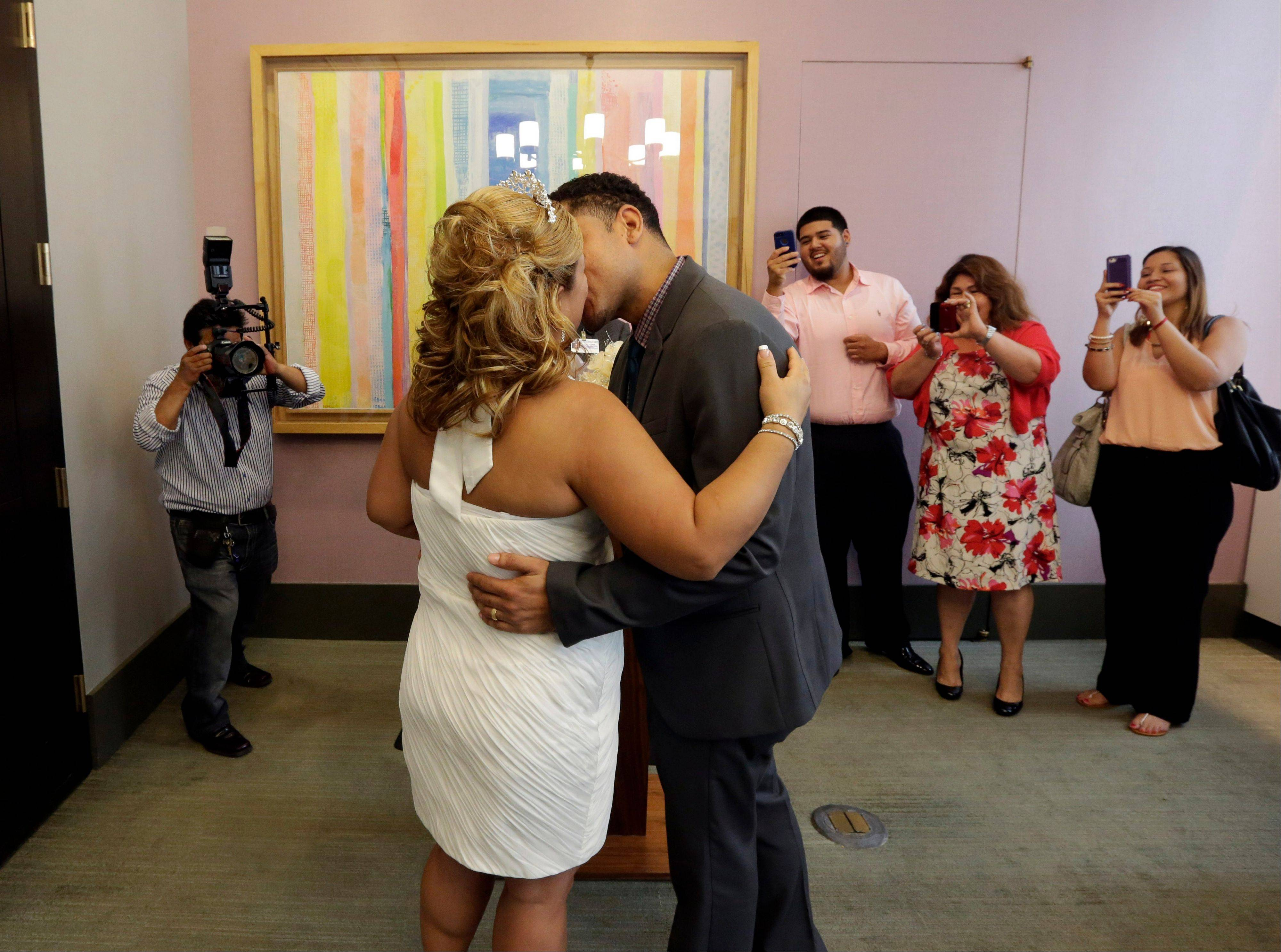 Wedding photographer Braulio Cuenca, left, captures the moment as groom Jorge Mejia and bride Irma Aguilar, of the Bronx borough of New York, kiss after their ceremony, inside a chapel at New York's Office of the City Clerk.