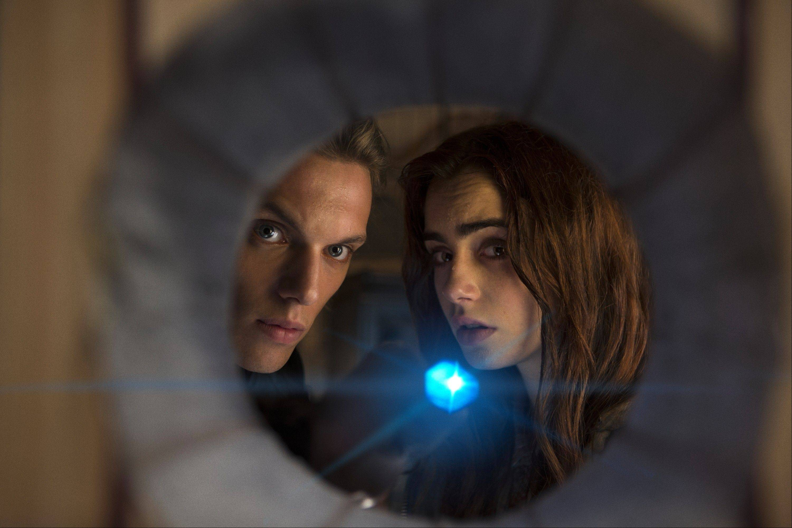 "Jace (Jamie Campbell Bower) and Clary (Lily Collins) spy on demonic activity in the hilariously bad fantasy adventure ""Mortal Instruments: City of Bones."""