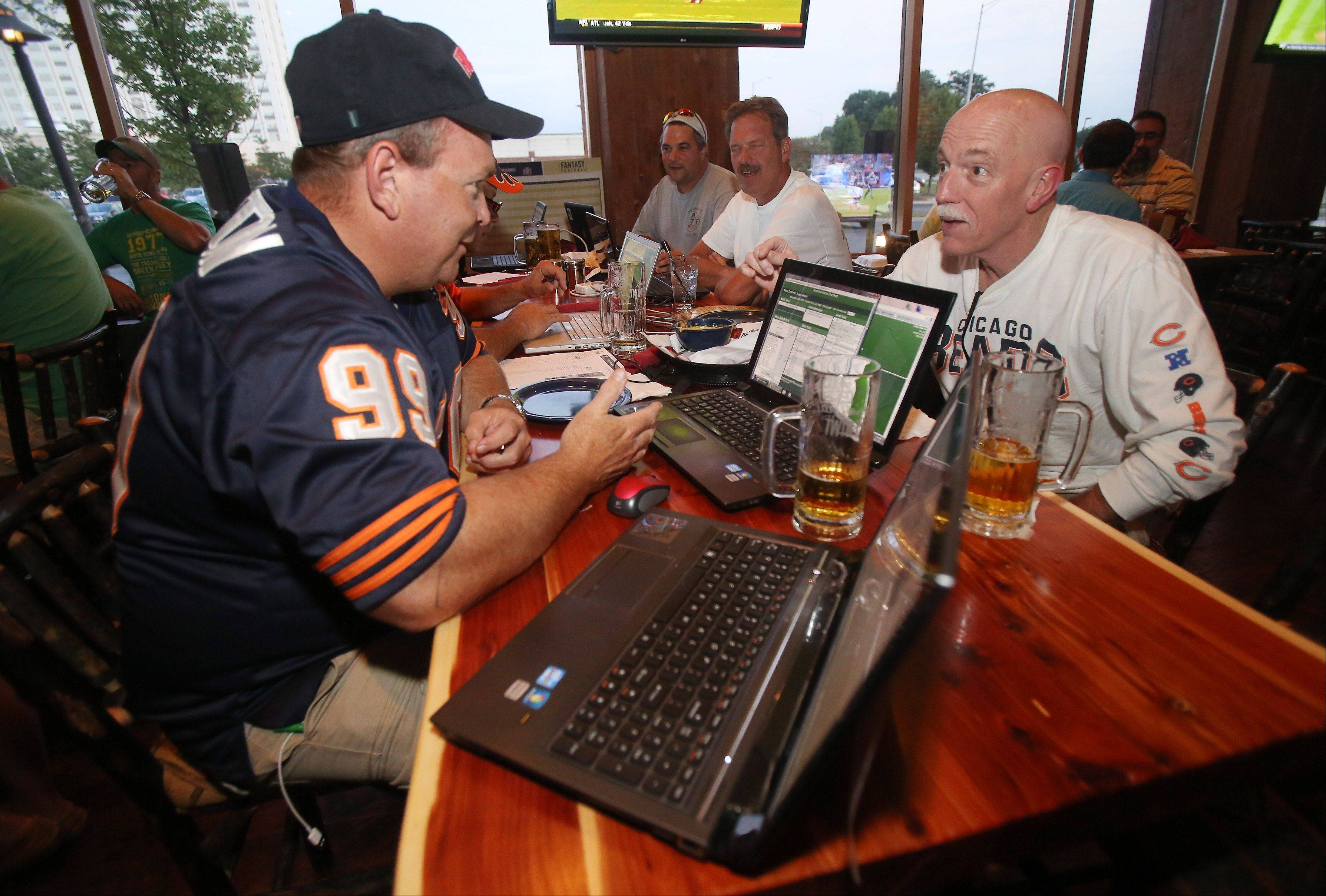 Northbrook firefighter Ken Morton, left, and retired firefighter Jim Lee work on their fantasy football teams with other Northbrook firefighters as they watch the Chicago Bears football game at Twin Peaks in Wheeling.
