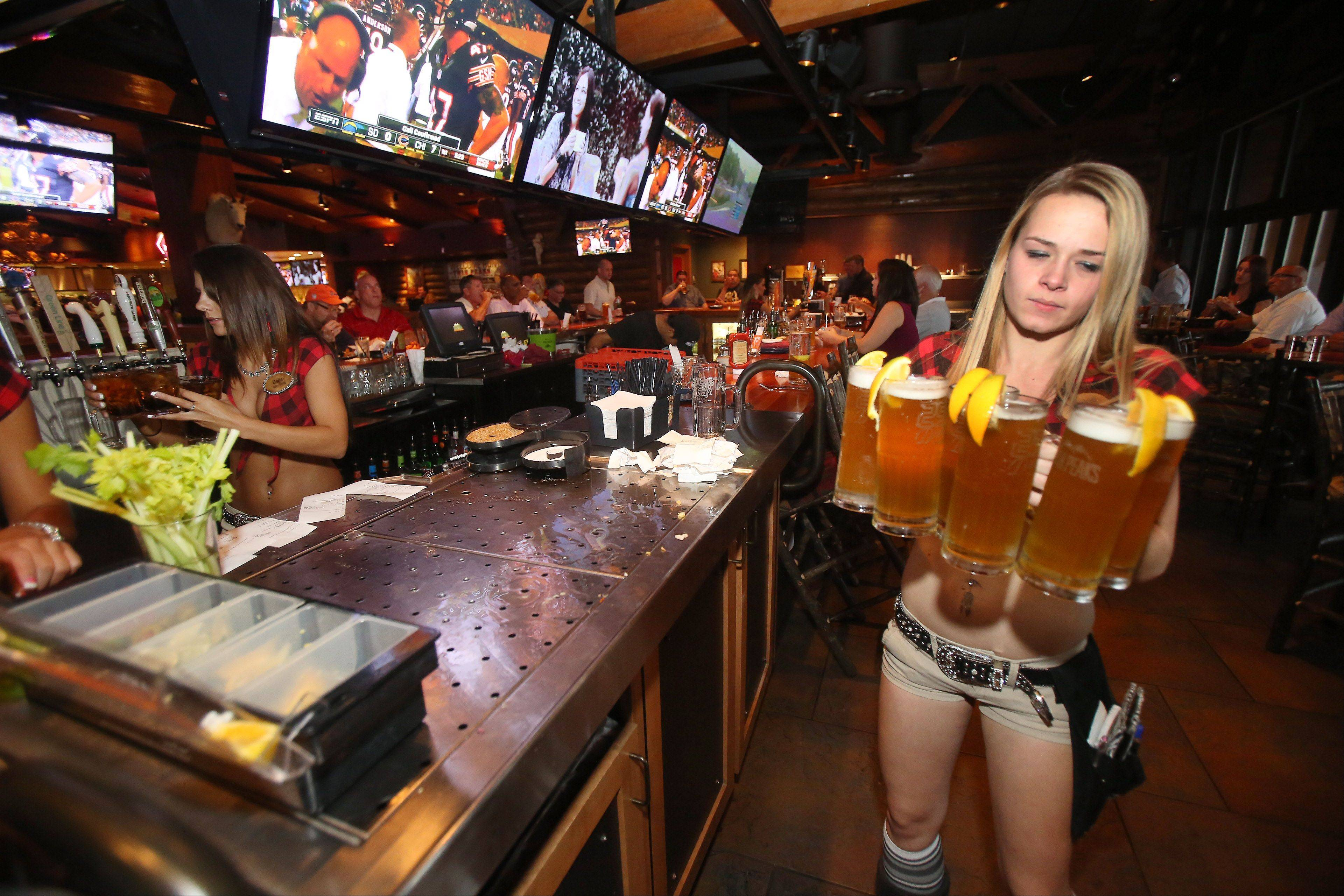 Server Jackie Malczynski delivers several beers to customers in the bar at Twin Peaks.
