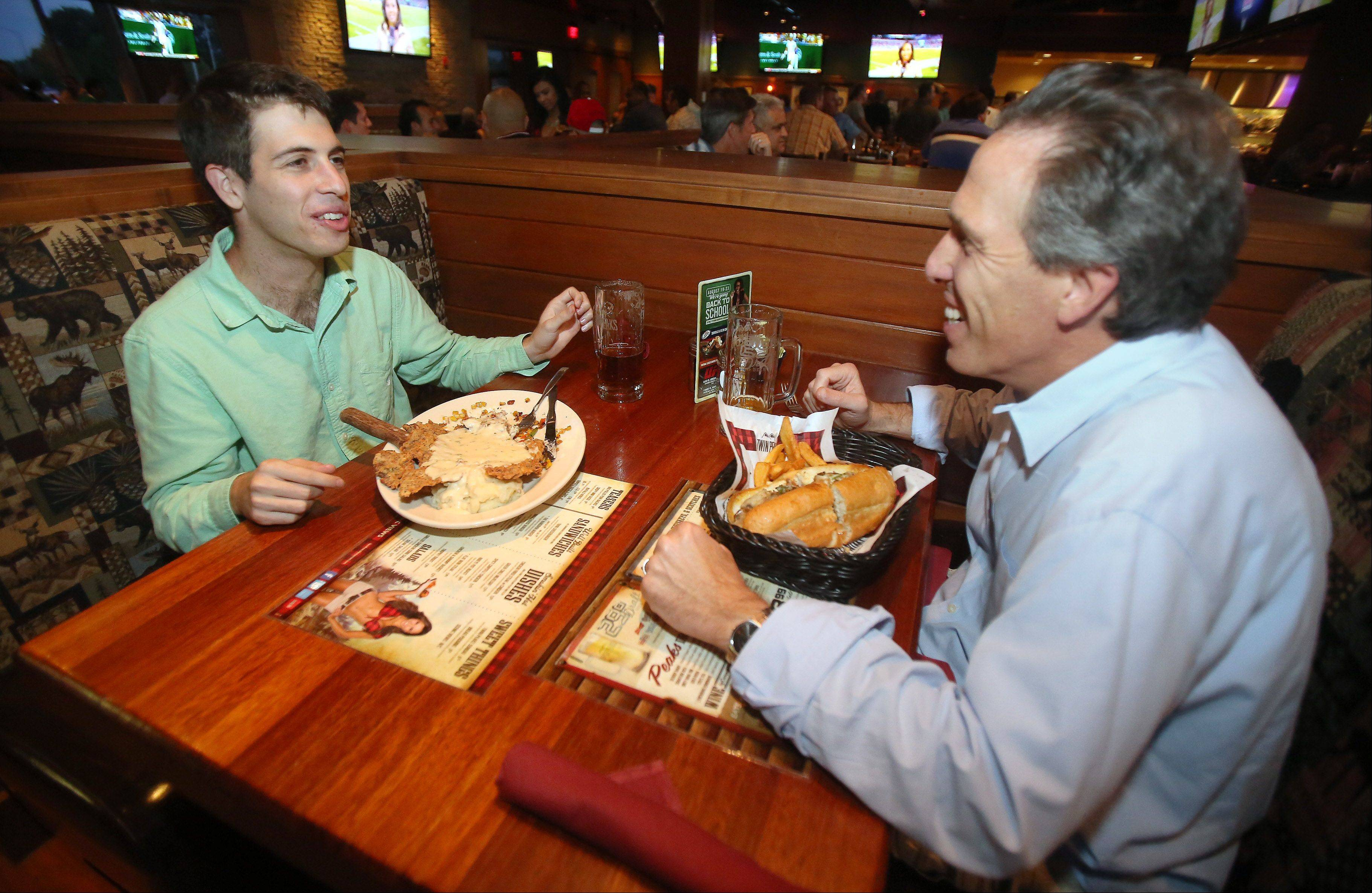 Daniel Cohen, left, of Buffalo Grove enjoys an oversized chicken-fried steak as he has dinner with his father, Mike, at Twin Peaks.