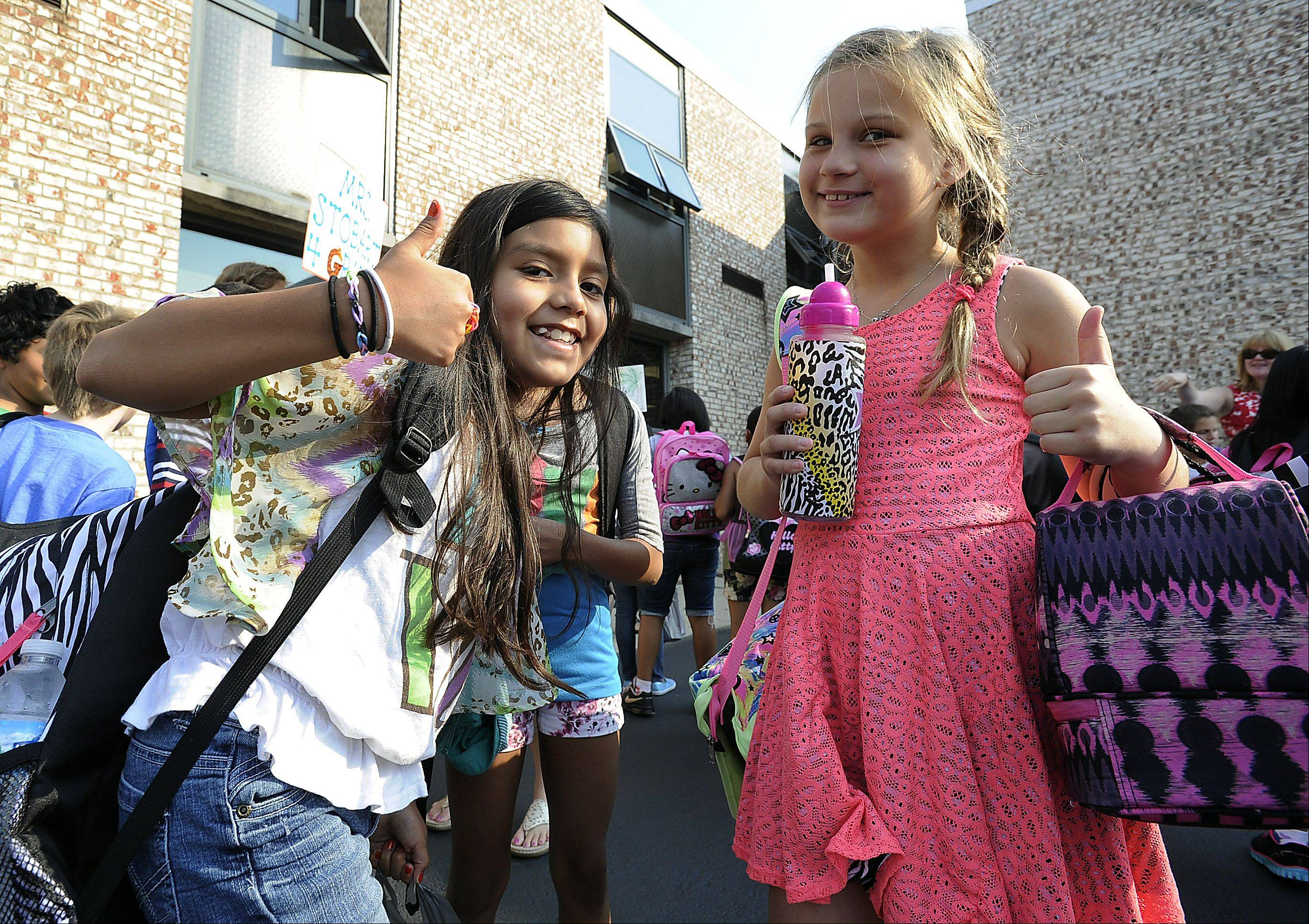 Hanna Gajek, 9, right, and her friend Samai Manzo, 9, give a big thumbs-up to the first day back to the 4th grade at Field Elementary School in Wheeling on Wednesday.
