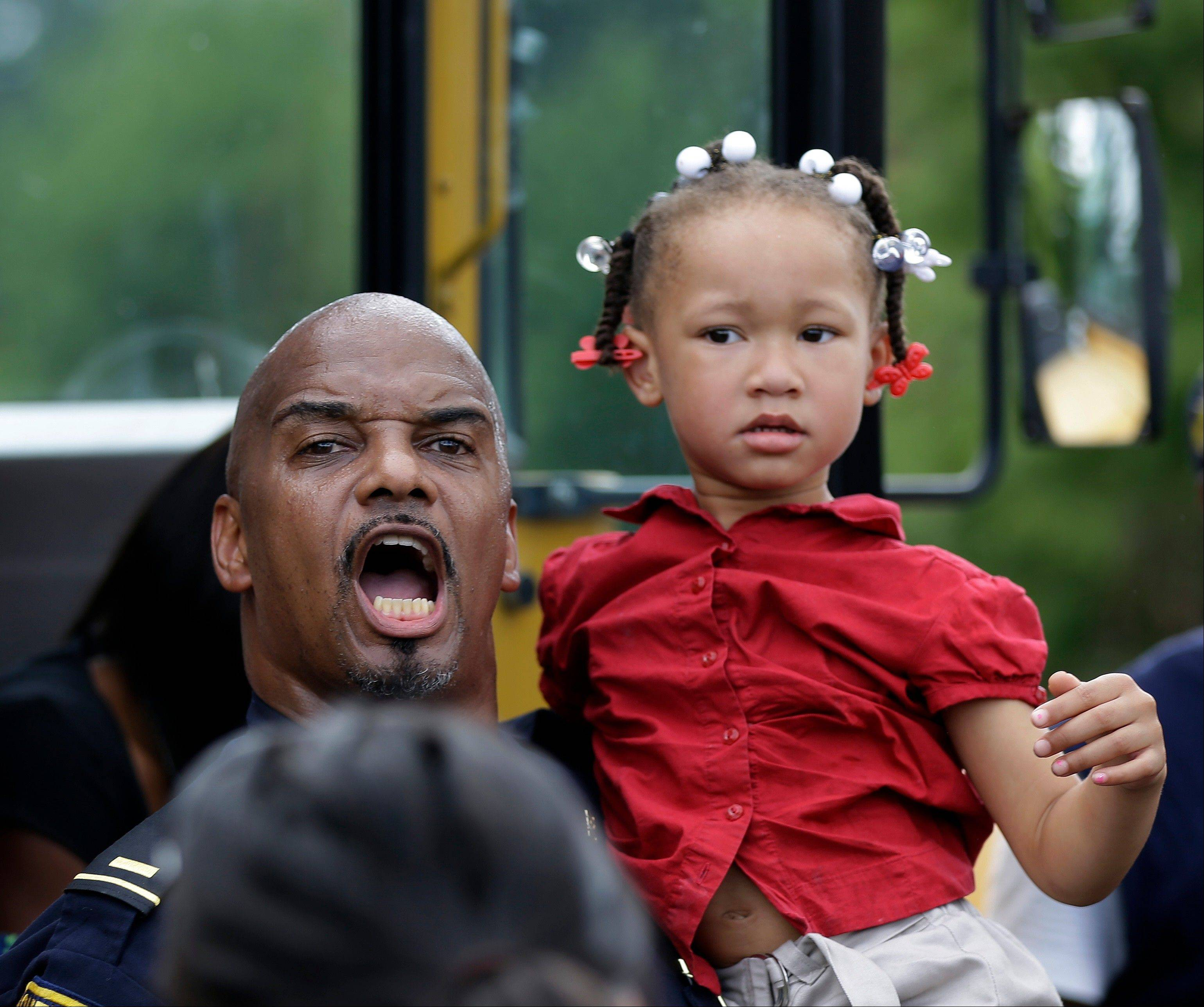 A police officer helps a child off a school bus carrying students after a shooting at Ronald E. McNair Discovery Learning Academy in Decatur, Ga., on Tuesday, Aug. 20, 2013. Superintendent Michael Thurmond says all students at the school east of Atlanta are accounted for and safe and that he is not aware of any injuries.