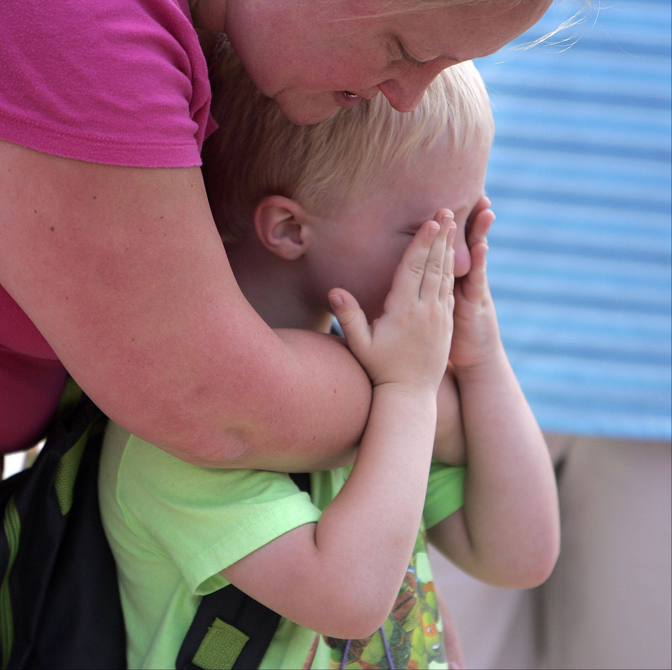 Sebastian Gruener, 5, is comforted by his mom, Coreen Larson, before Tuesday's first day of school at H.C. Storm Elementary School in Batavia. Sebastian, who was originally reluctant about kindergarten, walked right into class with the rest of the students.