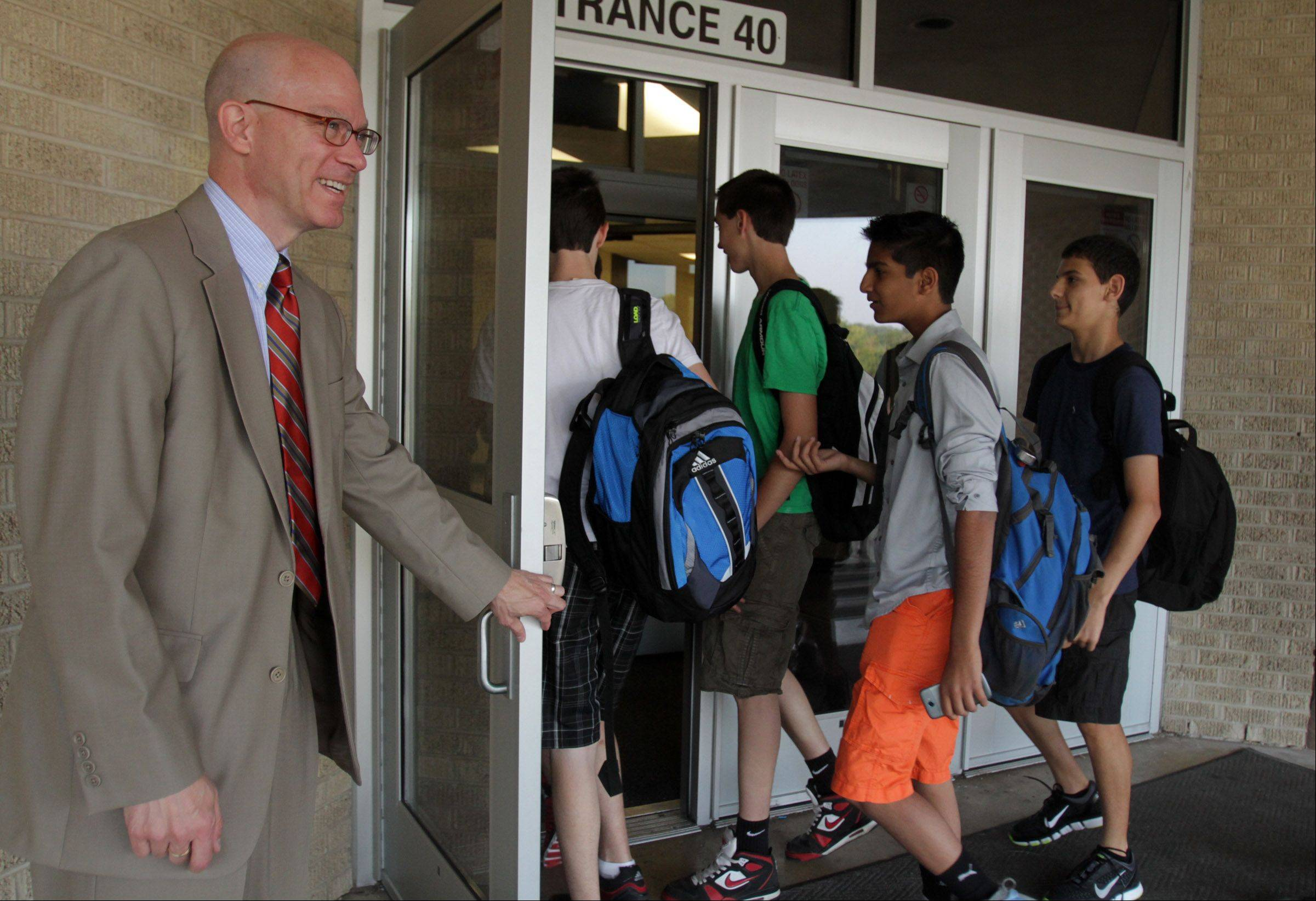 Jeff Arnett, spokesman for Barrington Unit District 220, holds the door open for students entering Barrington High School on the first day of school Tuesday.