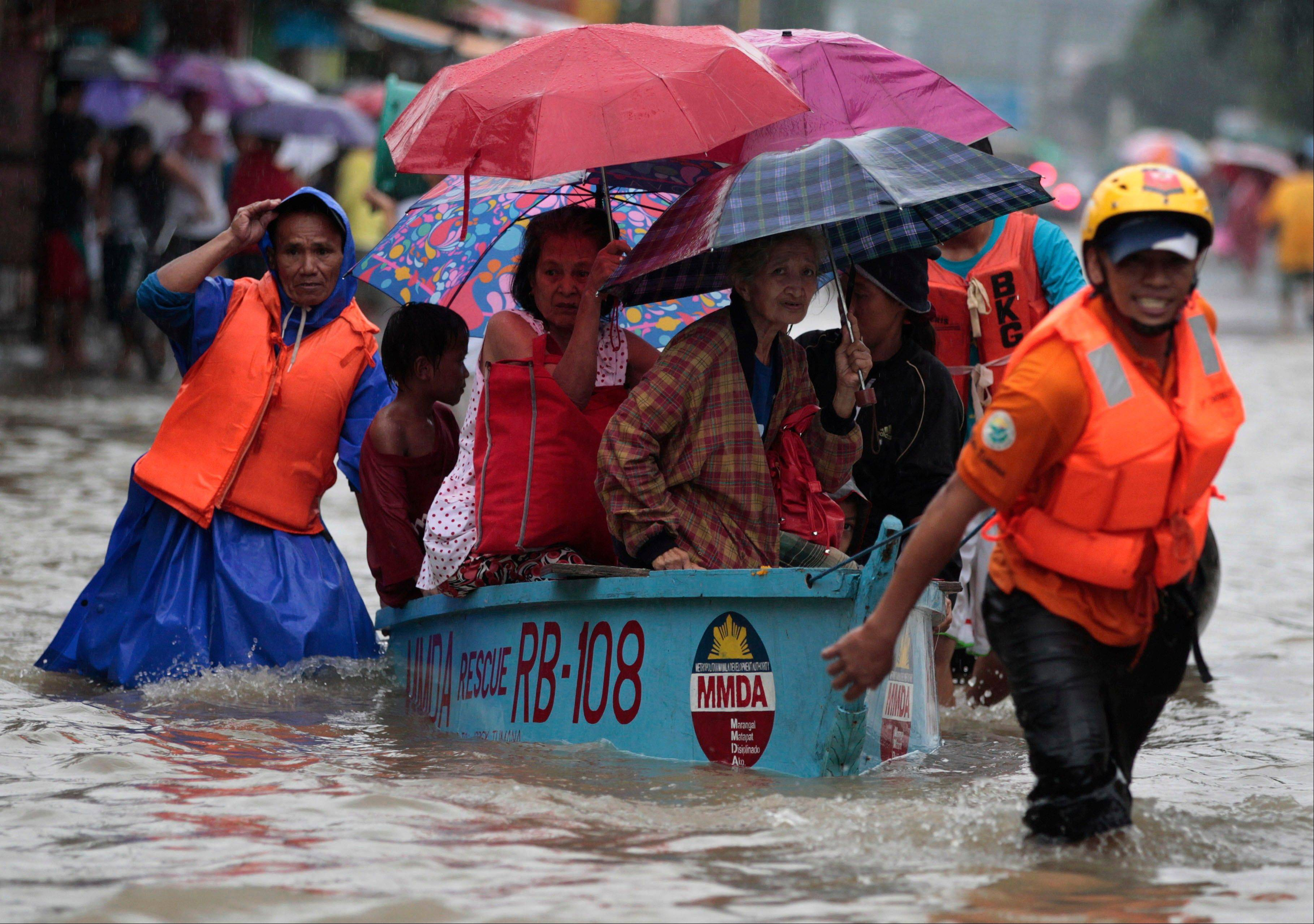 Rescuers pull a boat carrying residents as they enforce evacuation at an area flooded due to a swollen river in Marikina city, east of Manila, Philippines Tuesday, Aug. 20, 2013. Some of the Philippines' heaviest rains on record fell for a second day Tuesday, turning the capital's roads into rivers and trapping tens of thousands of people in homes and shelters. The government suspended all work except rescues and disaster response.