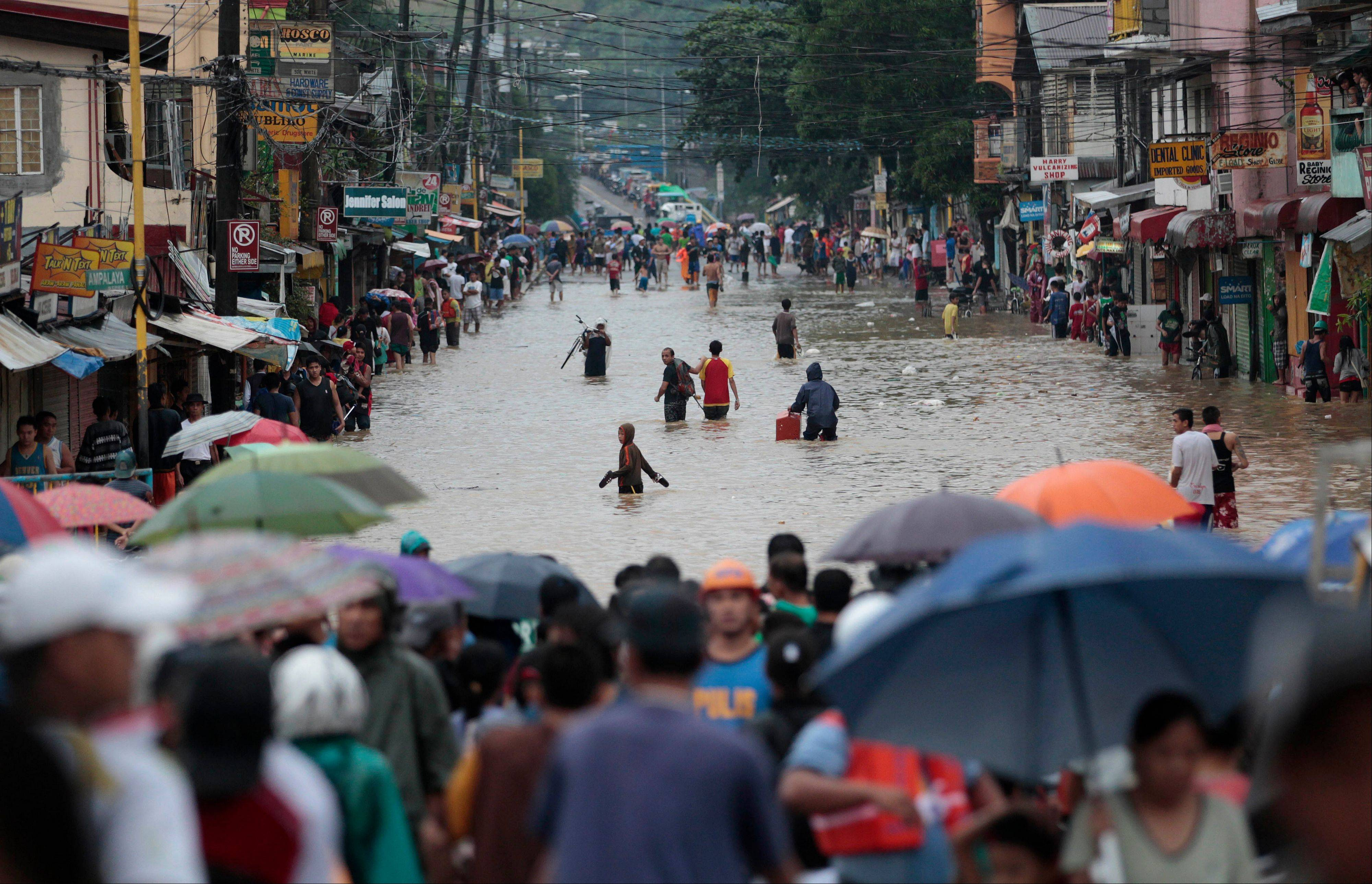 A crowd watches as residents cross a flooded street to evacuate to higher grounds in Marikina city, east of Manila, Philippines on Tuesday, Aug. 20, 2013.