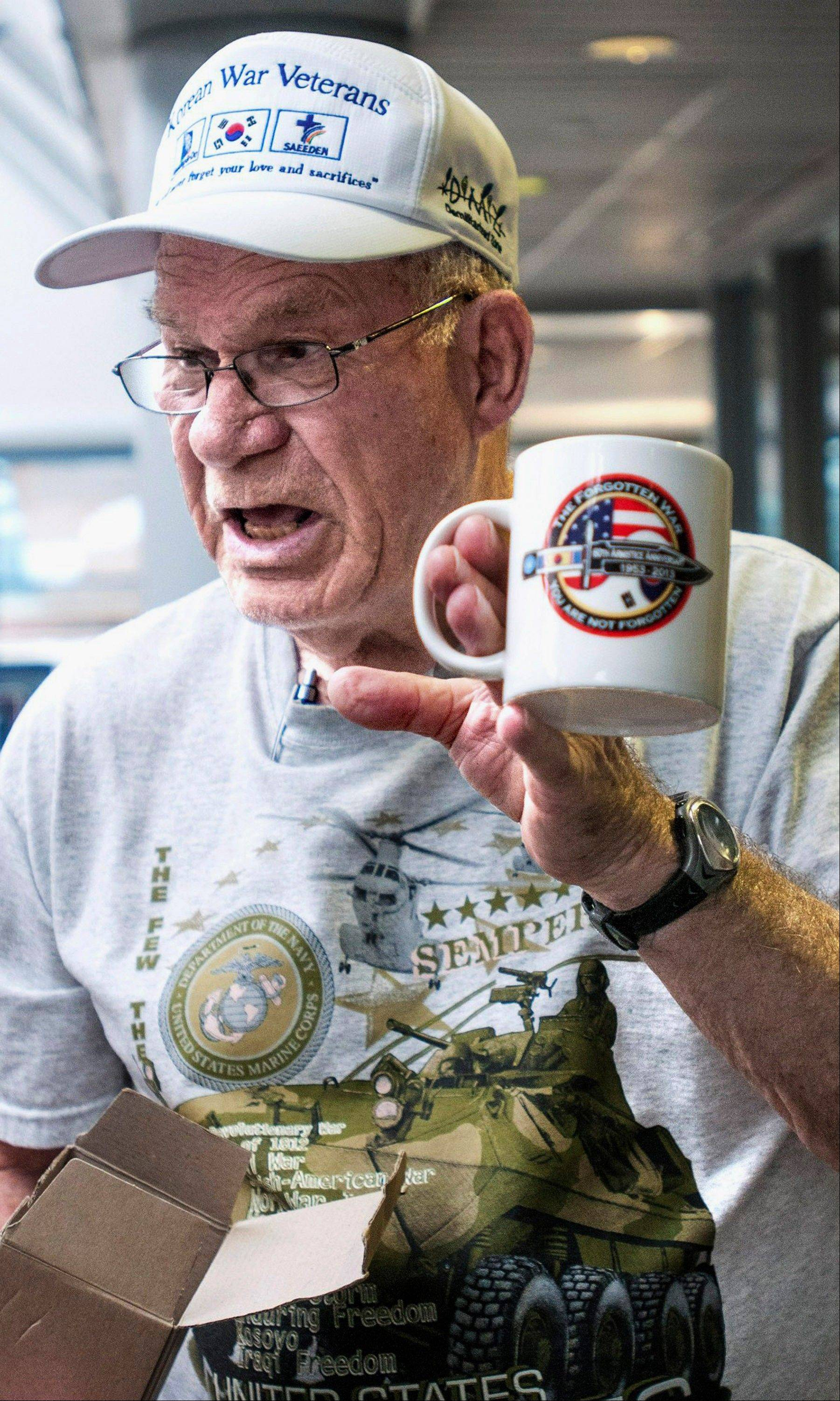 Marine veteran Sam McPheeters, 82, of Monticello, shows a mug that he received along with many other gifts on a five-day trip to South Korea to commemorate the 60th anniversary of the end of the Korean War after his arrival back to Willard Airport in Savoy.