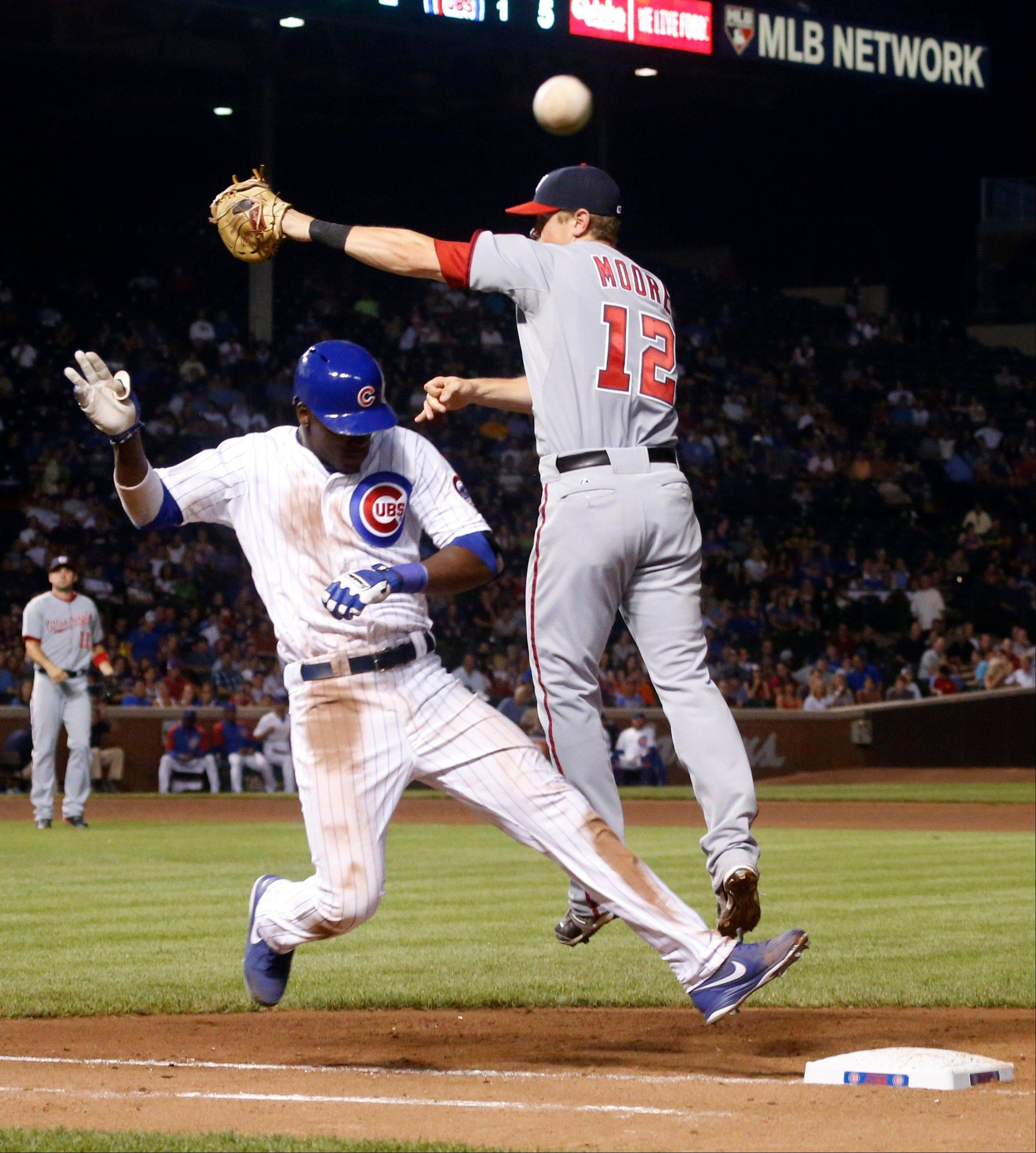 The Cubs' Junior Lake reaches first safely an errant throw from third baseman Ryan Zimmerman soars past as Nationals first baseman Tyler Moore during the fifth inning Tuesday.