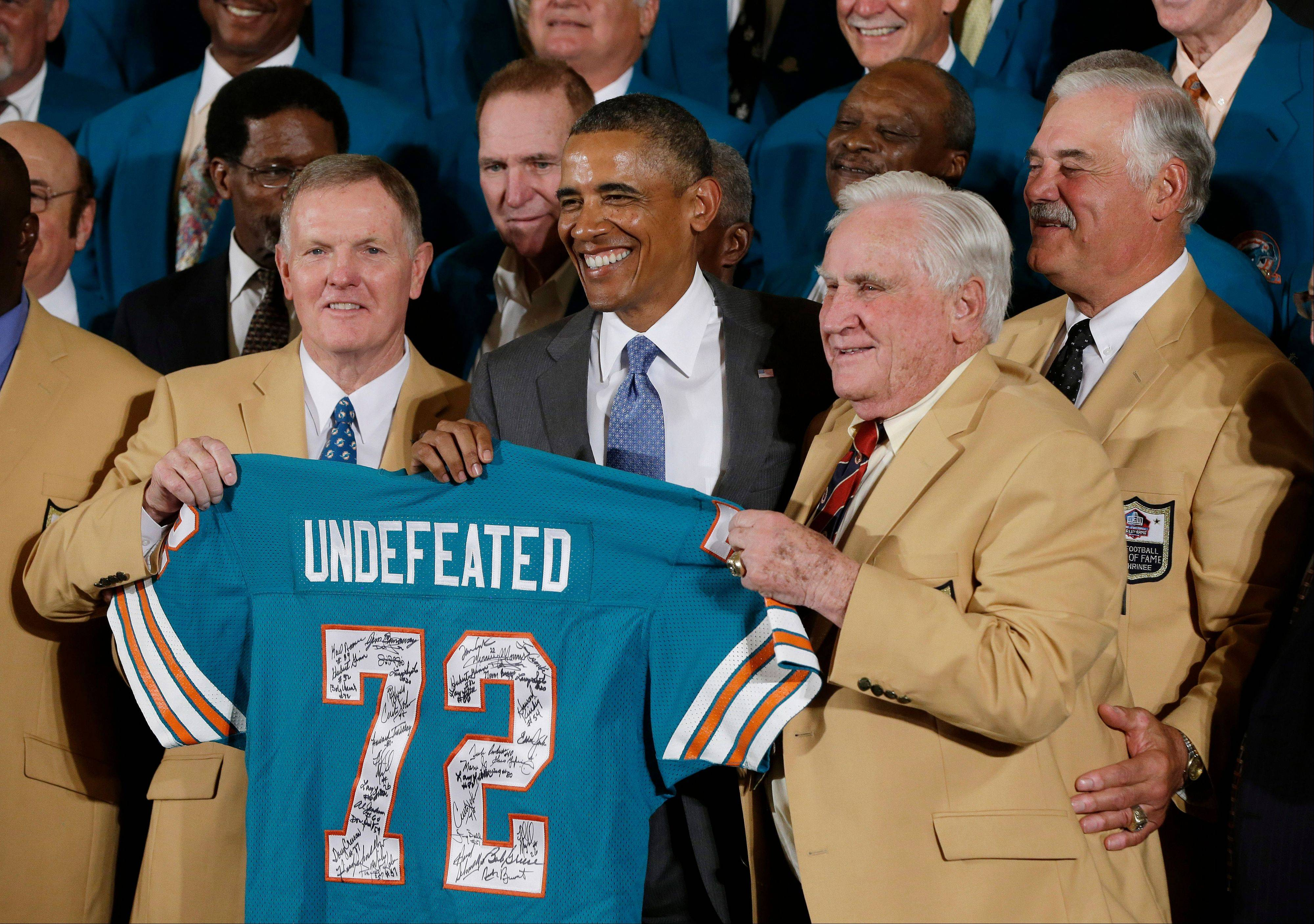 Former Miami Dolphins quarterback Bob Griese, left, and Hall of Fame Dolphins Coach Don Shula pose with President Barack Obama and a signed team jersey during a ceremony Tuesday in the East Room of the White House.