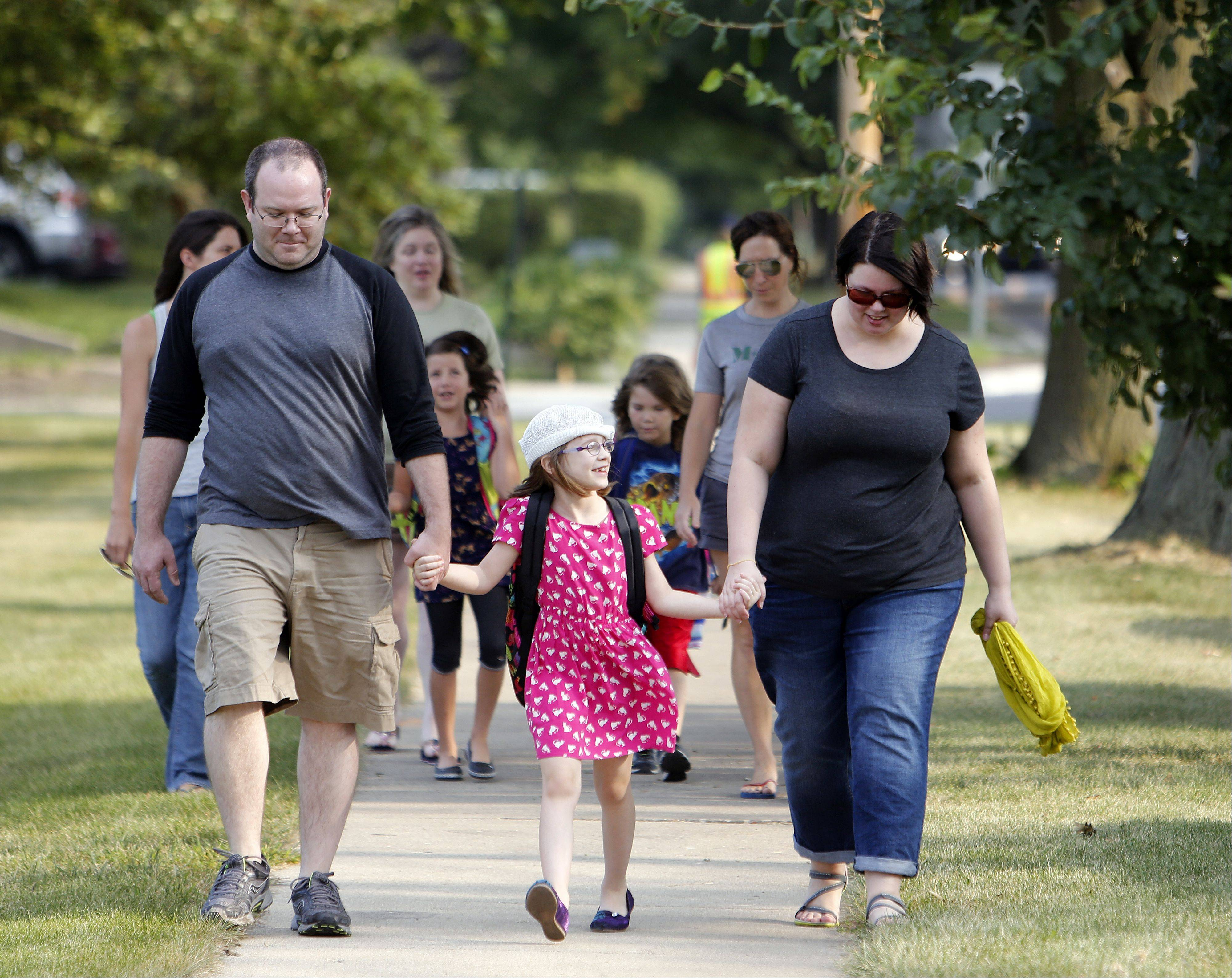Brian Hill/bhill@dailyherald.com Roger and Allyson Brewer walk hand in hand with their daughter Anya, 7, who was on her way to her first day of second grade at Davis Primary School in St. Charles Wednesday.
