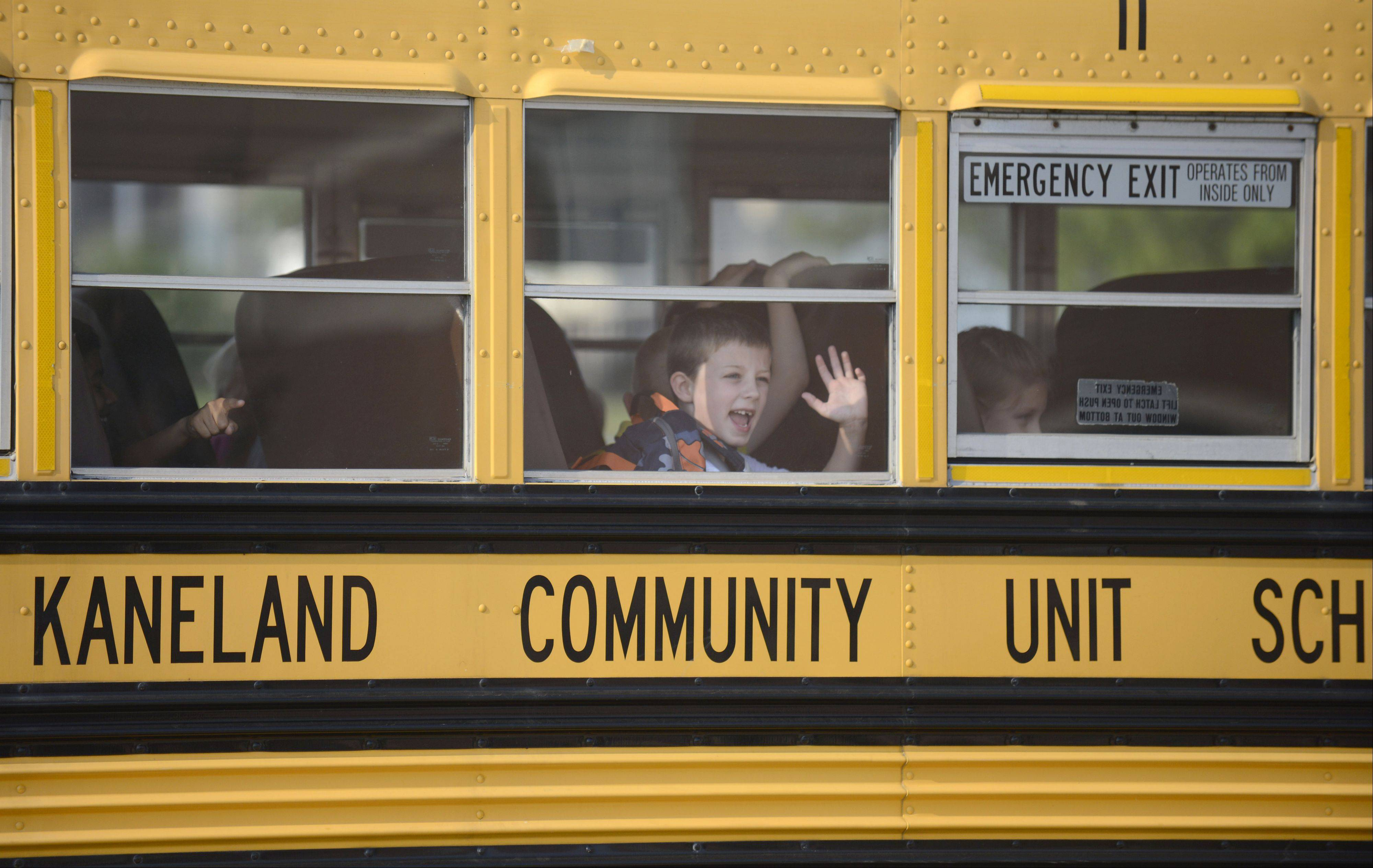 Blake Hansen, 7, waves to his parents Natalie and John as he arrives via bus at Kaneland Blackberry Creek Elementary School for the first day on Wednesday. Blake's parents met him as he got off the bus and saw him off to school.
