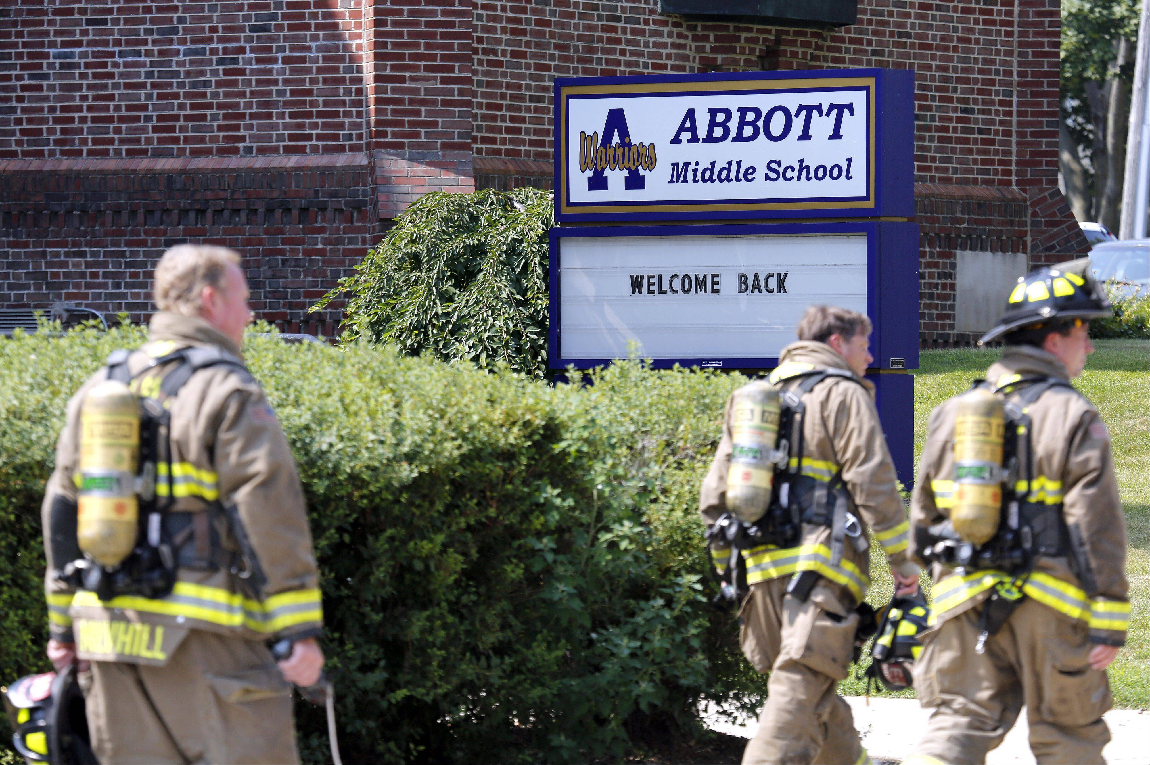 Firefighters head along the perimeter after a gas leak forced more than 540 students from Abbott Middle School to be relocated to Larkin High School for a few hours Wednesday. The leak was located near the southeast corner of the school grounds.