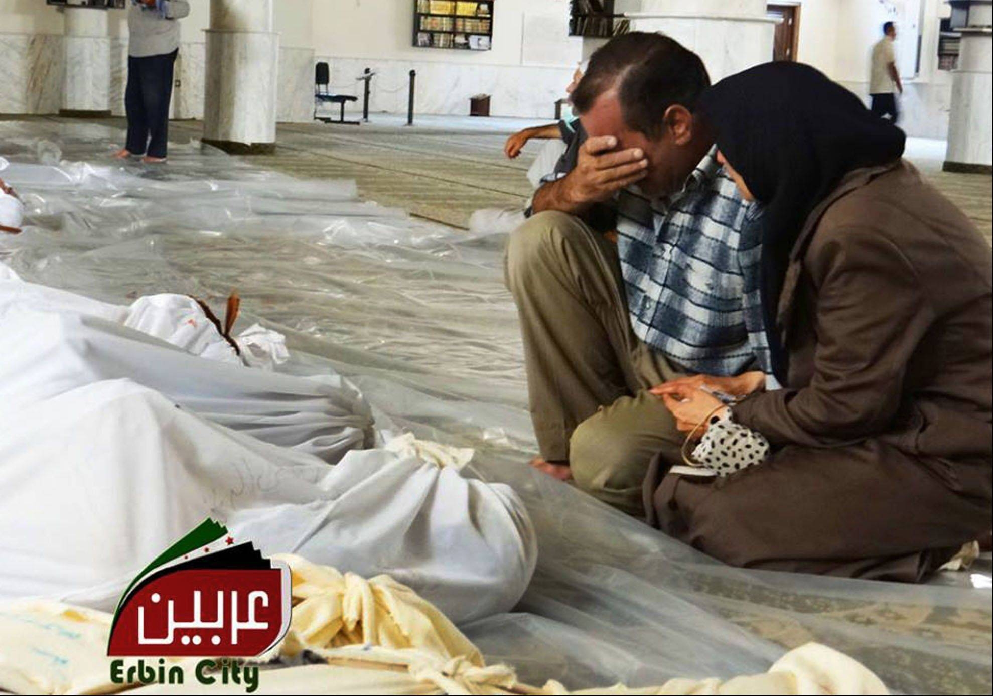 This citizen journalism image, Syrians mourn over the dead bodies, victims of an alleged poisonous gas attack fired by regime forces, according to activists Wednesday.