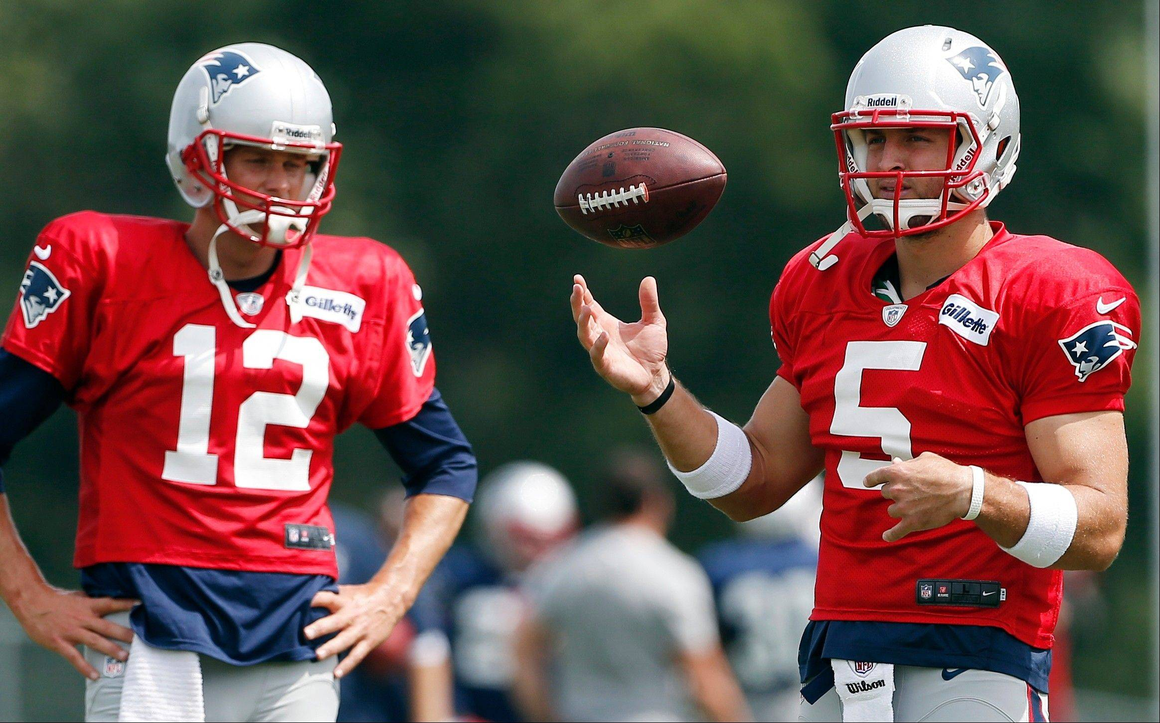 New England Patriots quarterback Tim Tebow (5) tosses a ball next to quarterback Tom Brady (12) during NFL football practice in Foxborough, Mass., Monday, Aug. 19, 2013. (AP Photo/Michael Dwyer)