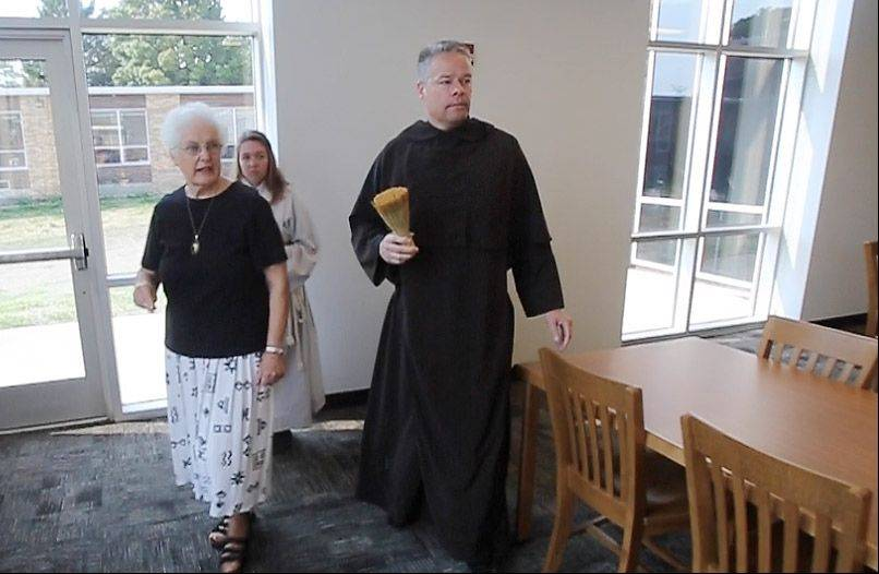 The Rev. Carl Markelz, Order of the Carmelites, and Sister Sheila O'Brien, Sisters of Charity of the Blessed Virgin Mary, perform the blessing of the spaces Wednesday at Carmel Catholic High School as part of the dedication of the new performing arts center and library expansion.