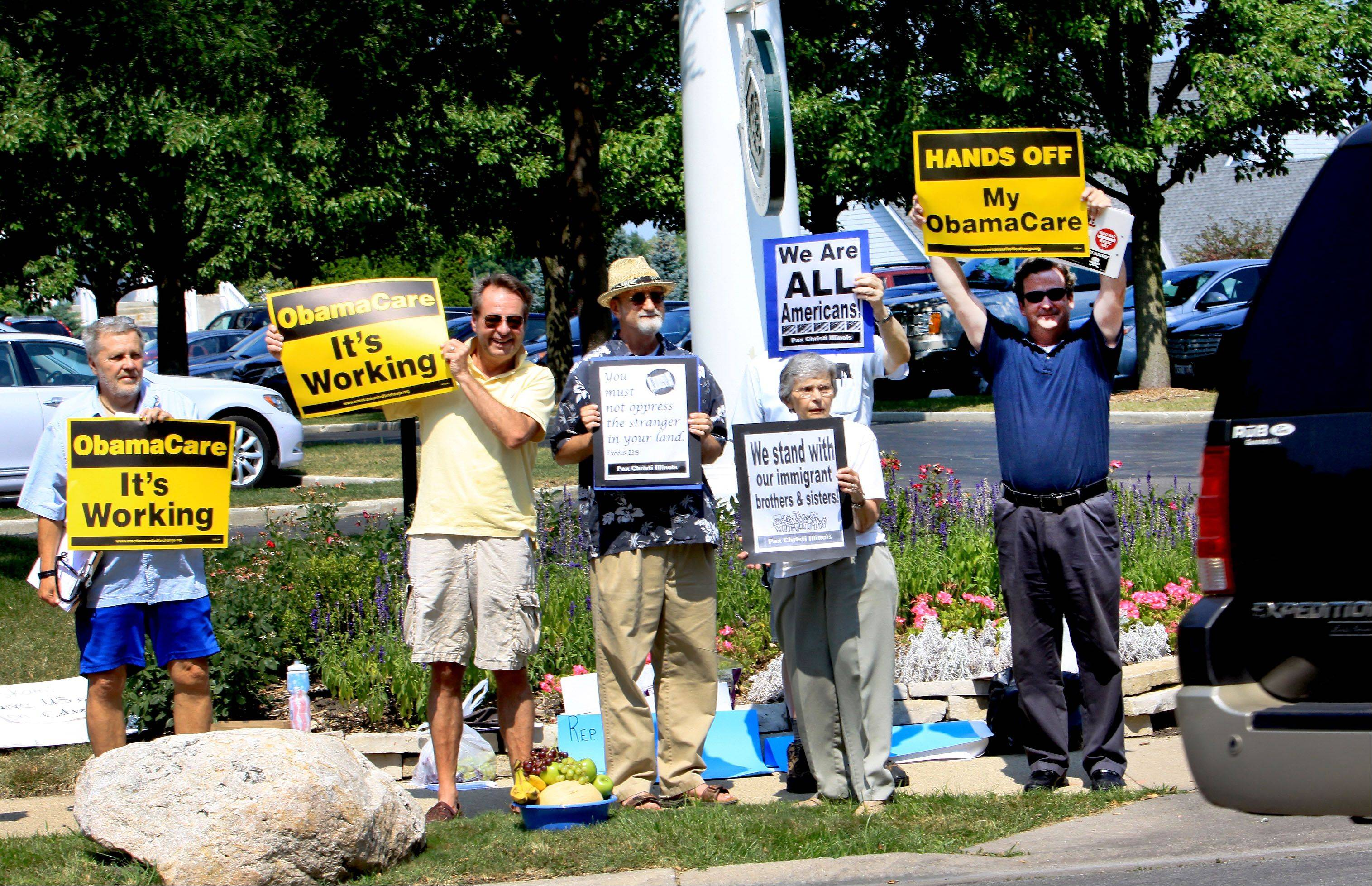 Groups gather to demonstrate outside Cress Creek Country Club in Naperville on Wednesday, where U.S. Rep. Peter Roskam was making an appearance.