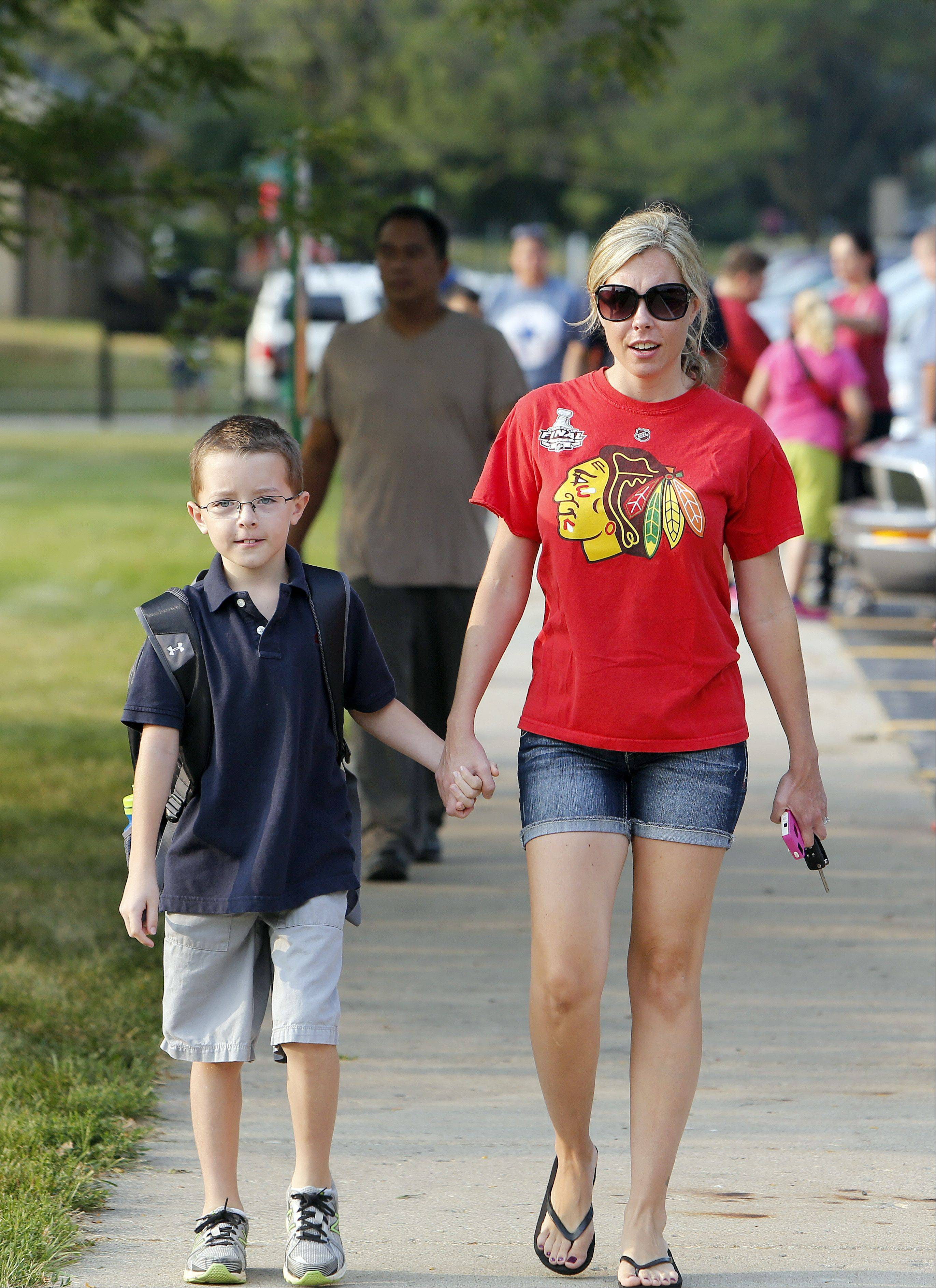Brian Hill/bhill@dailyherald.comJack Murphy, 8, walks with his mom Ashley on the way to the first day of school and third grade at Richmond Intermediate School in St. Charles Wednesday.
