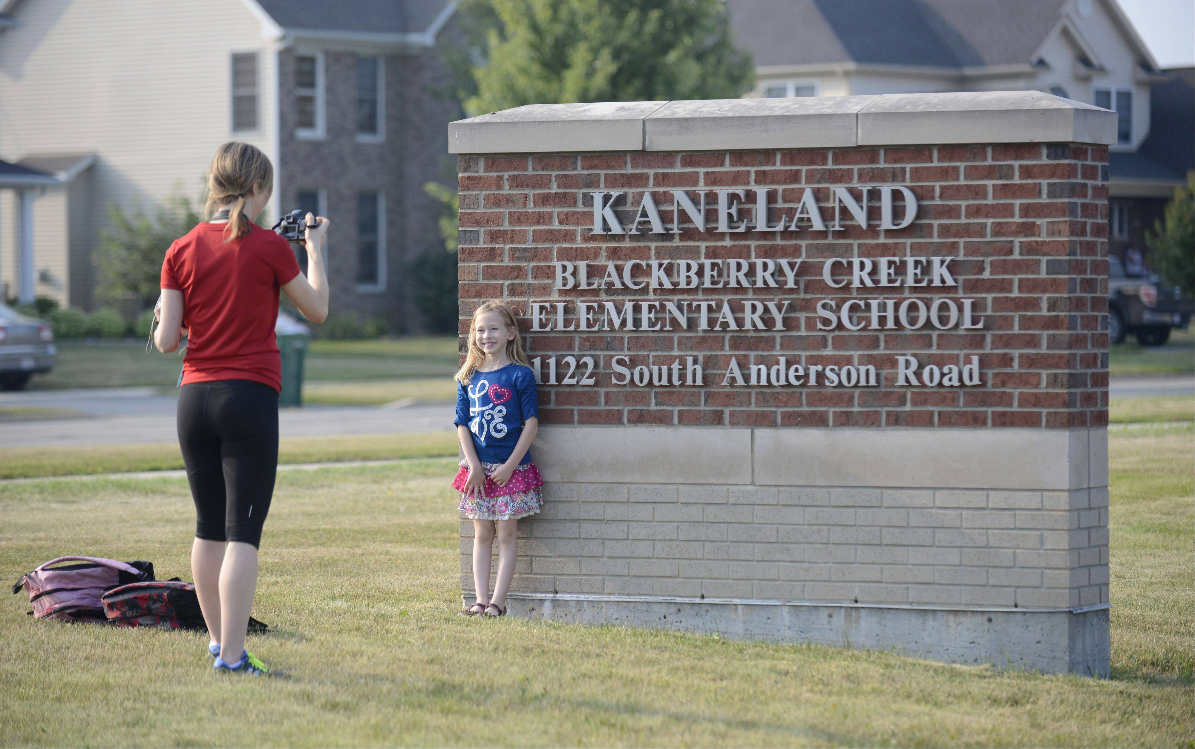 Laura Stoecker/lstoecker@dailyherald.comLaura Ryan takes a picture of her daughter, Alyssa, 8, as she and her younger brother, Ethan, 6, (hiding behind sign) take turns in front of the school sign for Kaneland Blackberry Creek Elementary School on the first day on Wednesday, August 21.