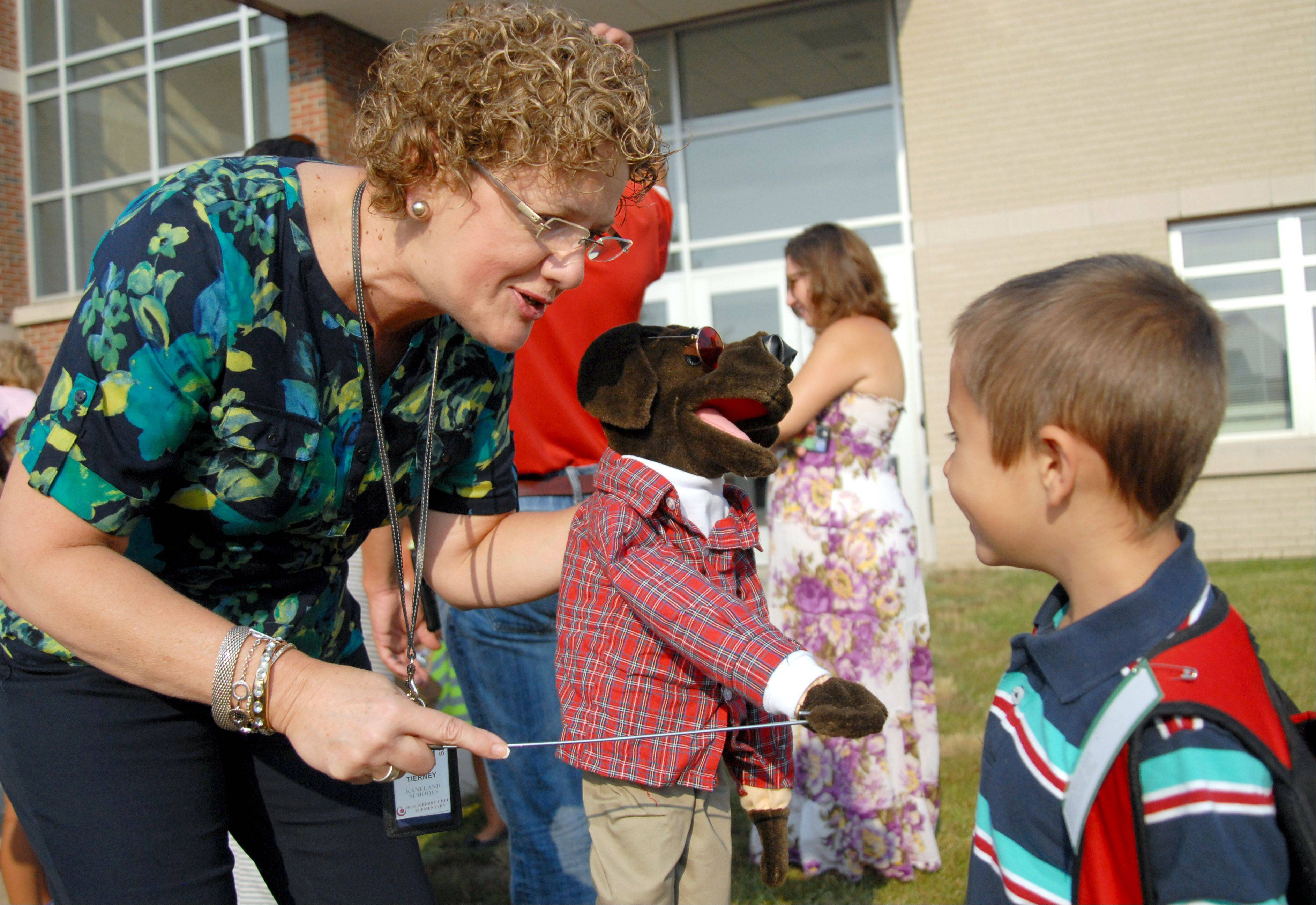 Laura Stoecker/lstoecker@dailyherald.comLiterary teacher, JoAnn Tierney, introduces Blackberry to the dog to first grader, Jason Vandeveire, 6, as students line up for the first day of school at Kaneland Blackberry Creek Elementary School on Wednesday, August 21.