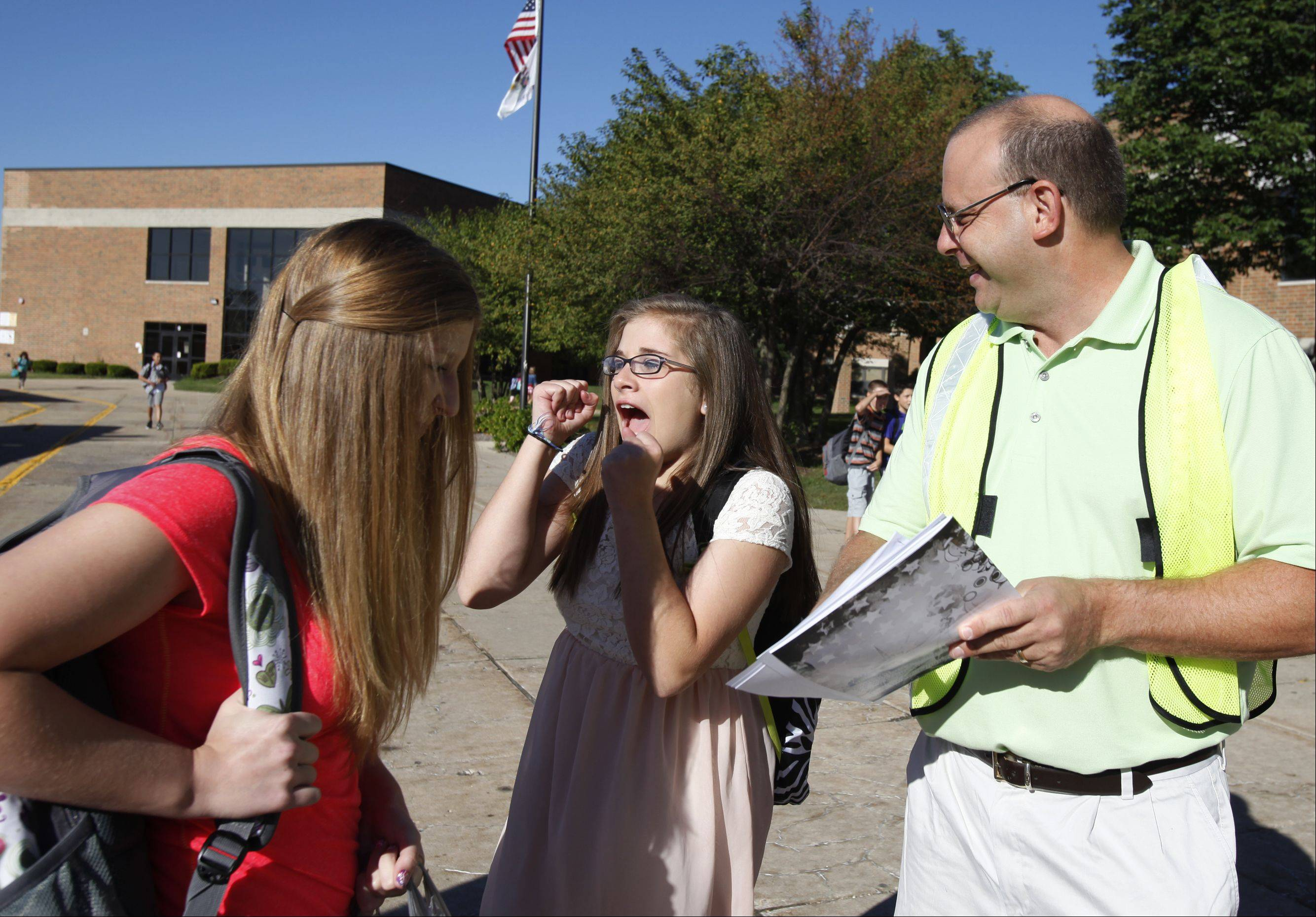 "Eighth-grader Allie Mandel, center, cheers as she learns what ""team"" she is in this year as she and fellow eighth-grader Jala Micic arrive at Westfield Community School for the first day of classes last week. At right is seventh-grade teacher Matt Skidmore. Students are grouped into ""teams"" of students for their core classes with certain teachers, and those details aren't known to the students until they show up on the first day."