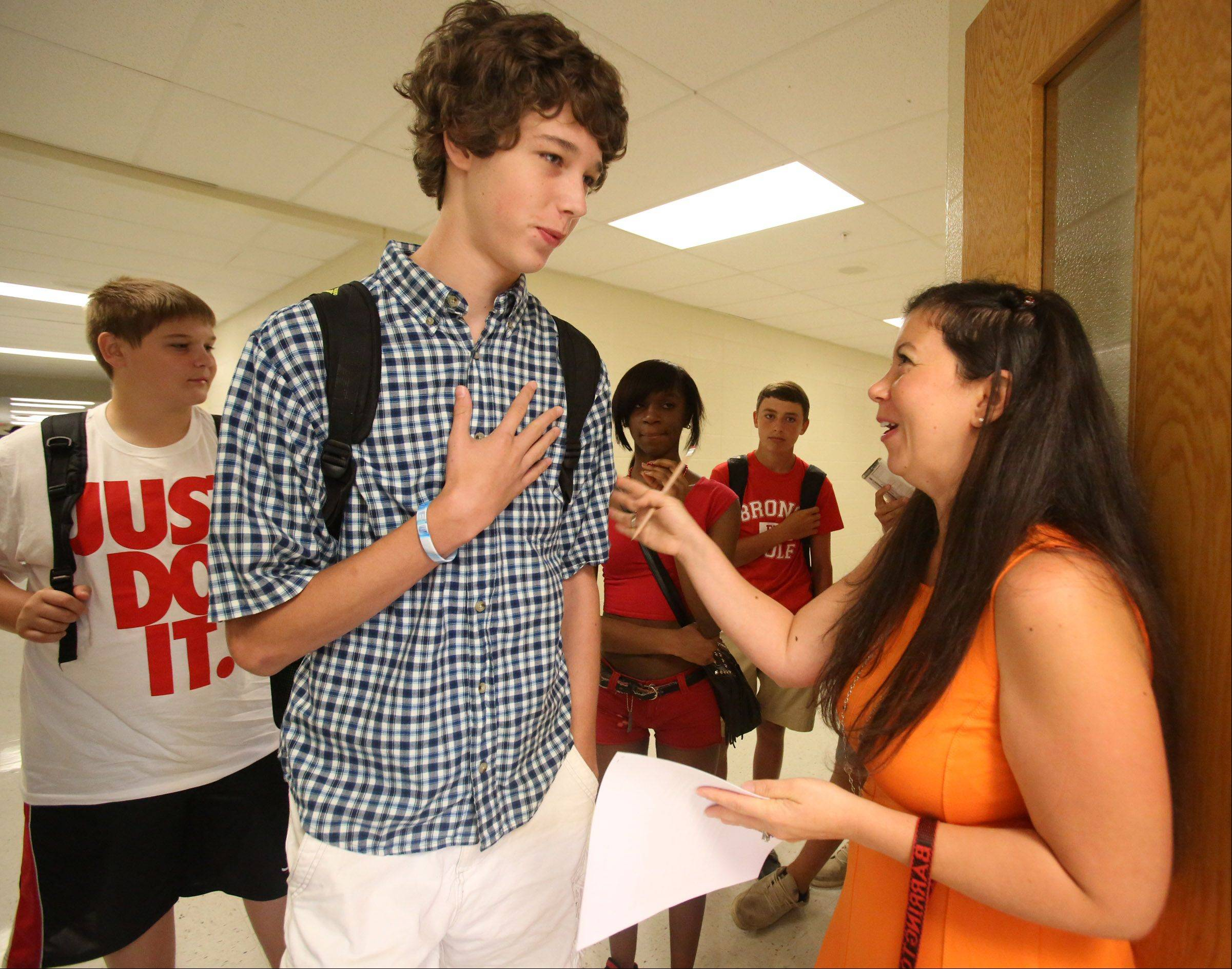 Thomas Murray is greeted by Spanish language teacher Lisa Nardiello for Spanish II class during the first day of school at Barrington High School on Tuesday.