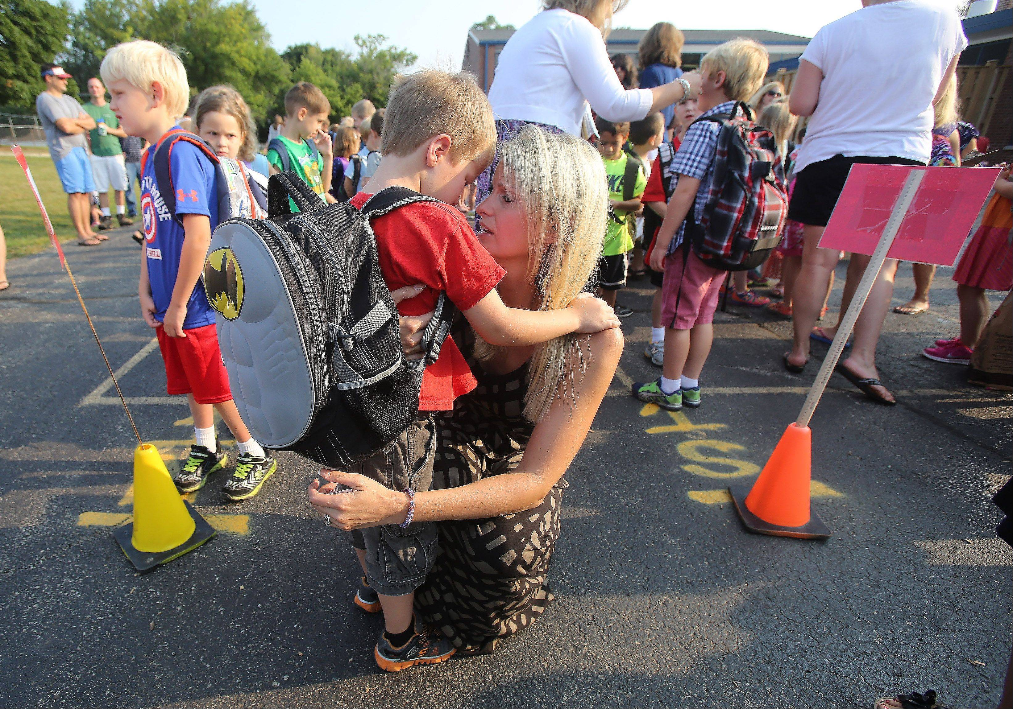 Kindergarten teacher Jennifer Saks talks with former student Bryer Seibert as he enters the first grade at Copeland Manor School in Libertyville Wednesday during the first day of classes.