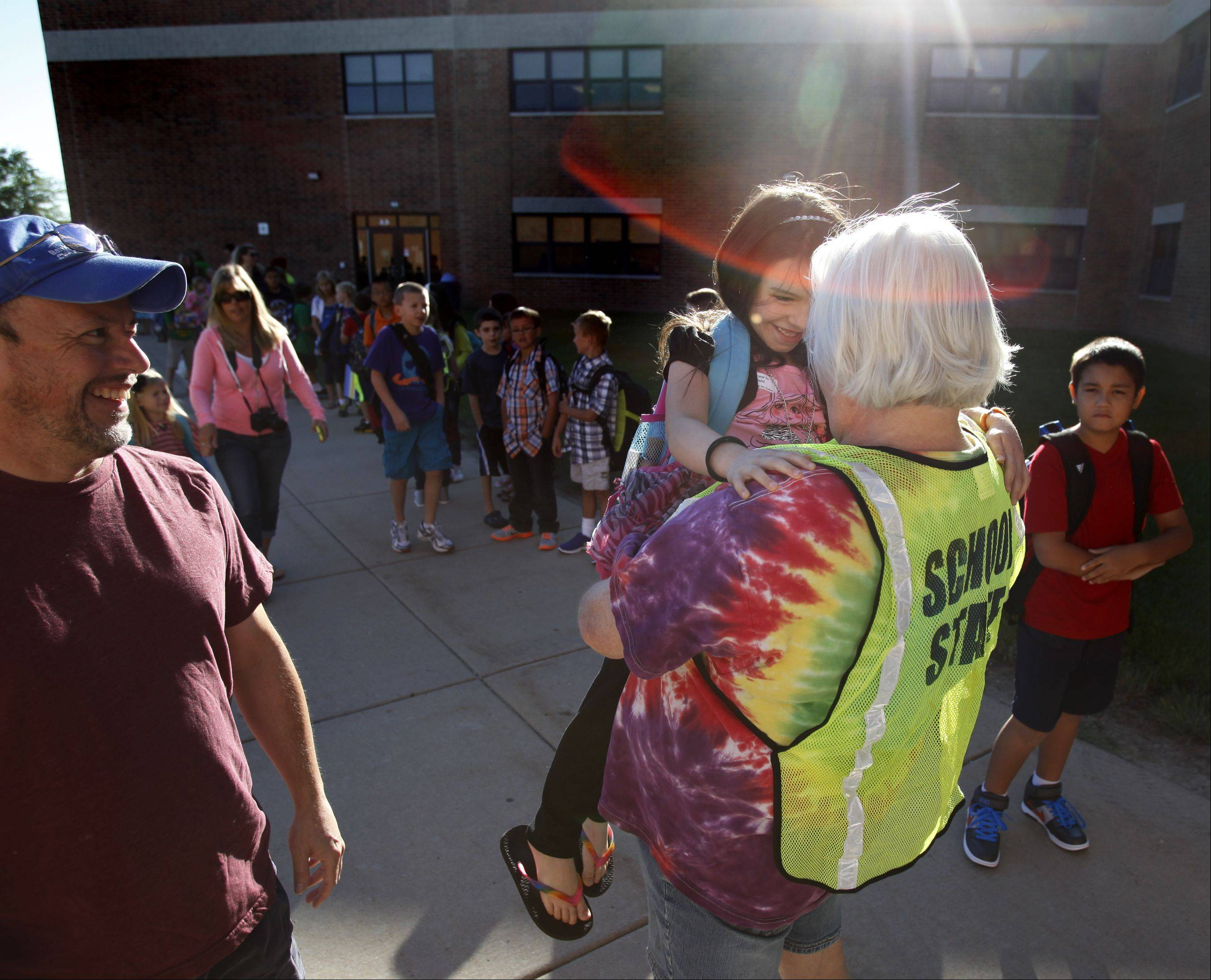 New kindergartner Ava Tousey jumps into the arms of third-grade teacher Michelle Soland as she arrives with other students at Westfield Community School last Wednesday for the first day of classes. Ava's father Mike is pictured at left.
