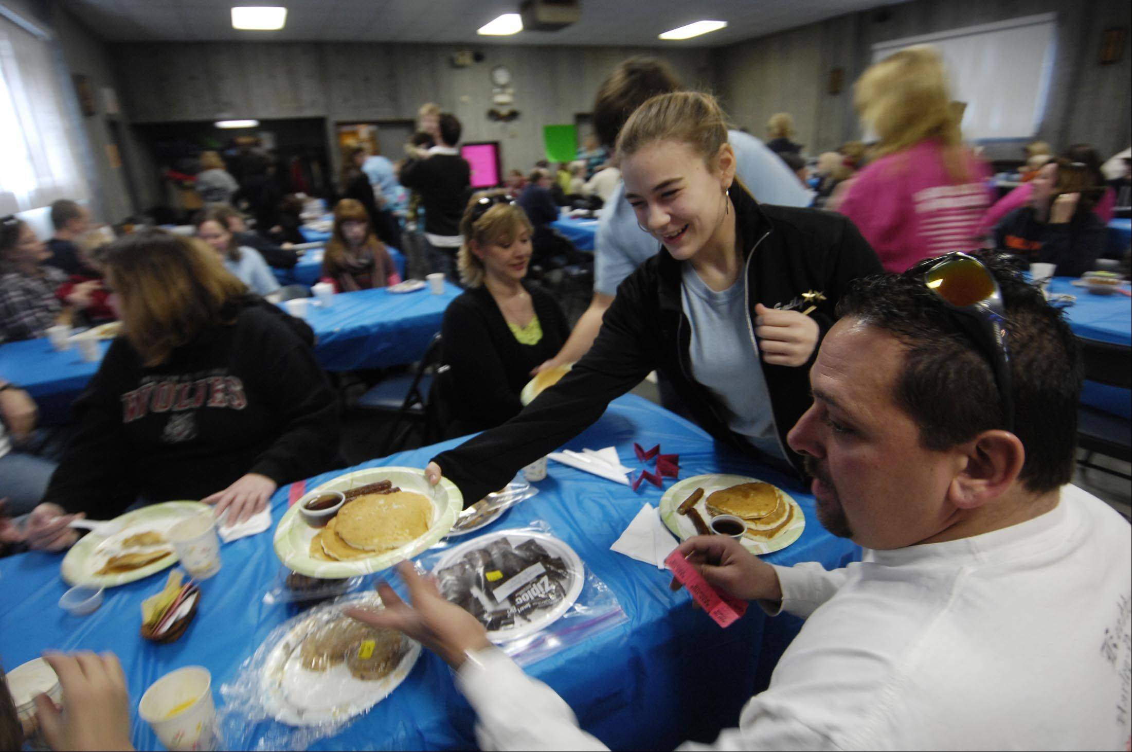 Emily Weyers and Nick Blaise, obscured, both 18, served plates of warm food last year at a pancake breakfast to benefit the Allegiance Youth Color Guard of Dundee. Weyers was struck and killed by a car as she walked along Algonquin Road.