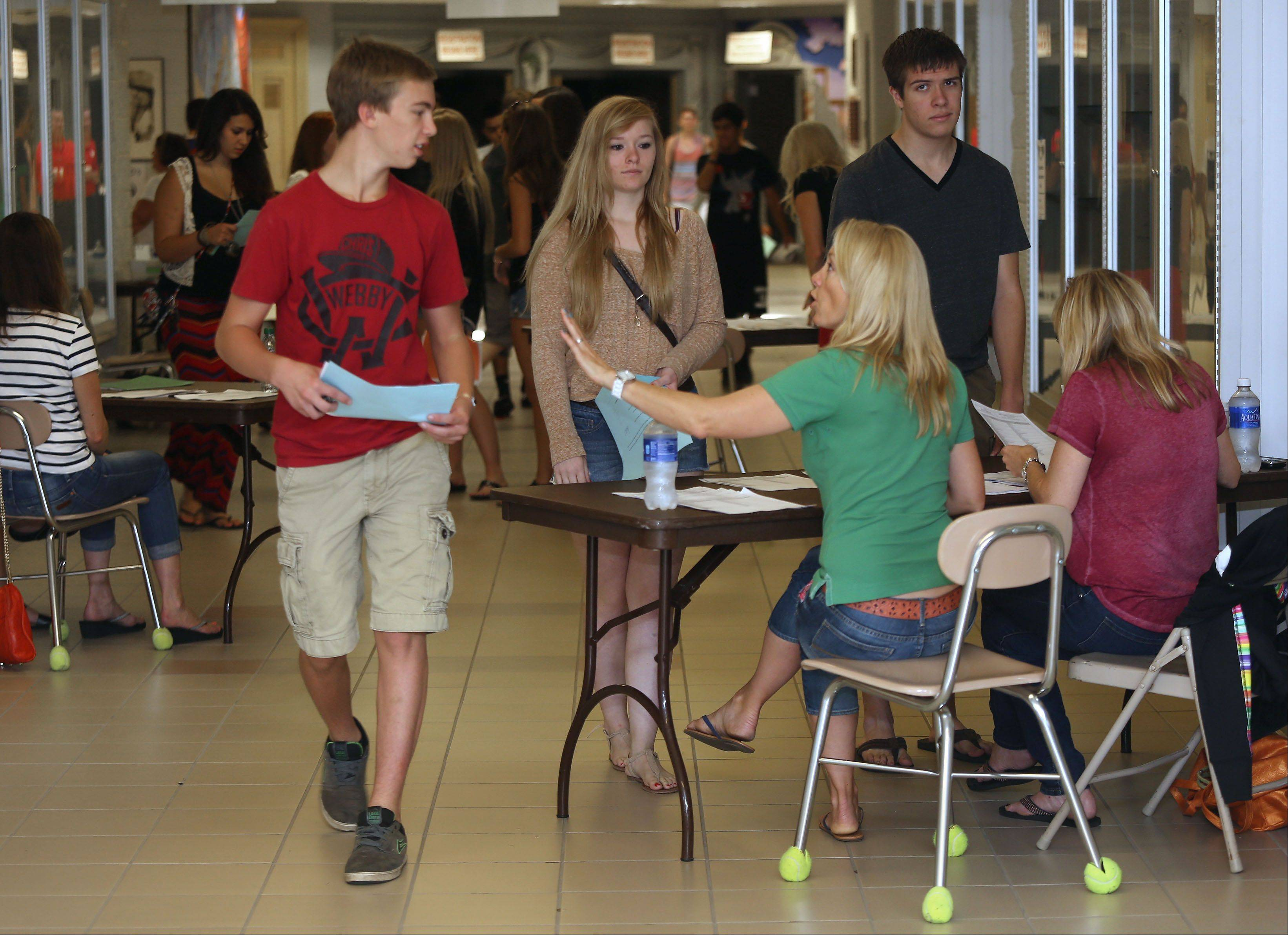 Junior Gunnar Samuelson is directed to where he picks up his ID after receiving his schedule from volunteer Hollie Free during recent registration activities at Barrington High School, where high school registration fees are $216.