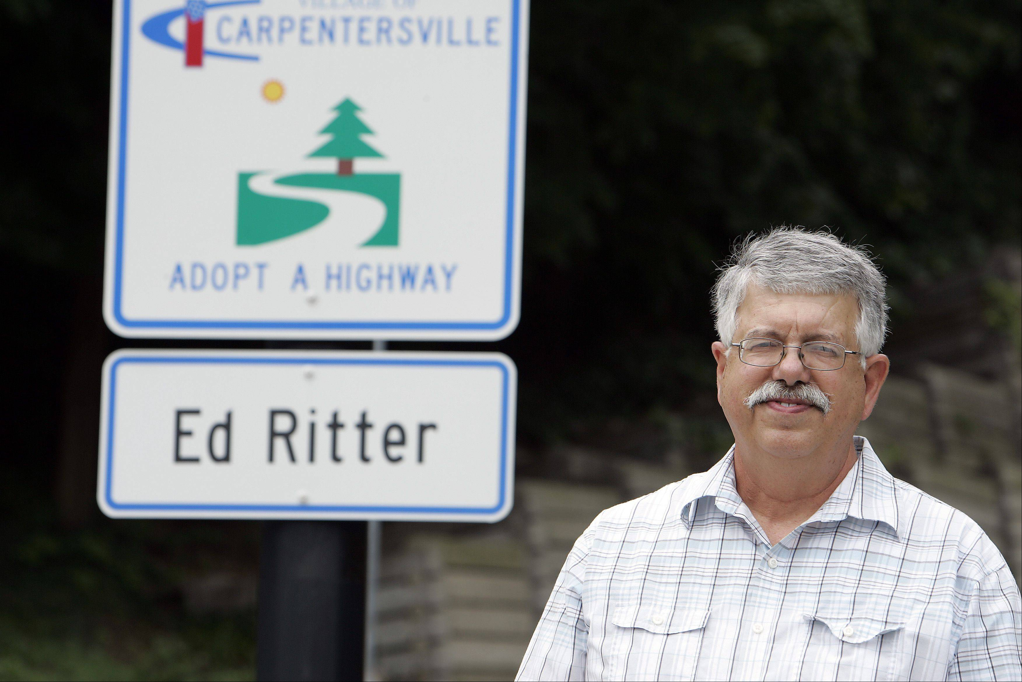 Village President Ed Ritter stands next to a sign along West Main Street in Carpentersville. Ritter, who lives not too far from the sign, is responsible for keeping this part of Main Street clean.