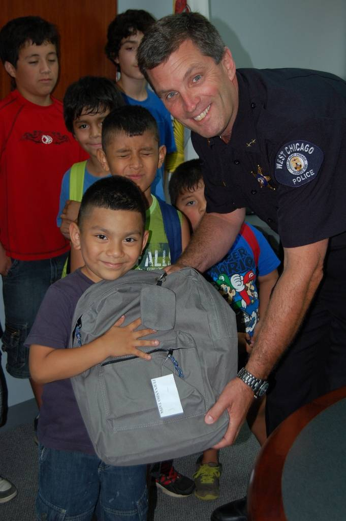 Deputy Chief Michael Uplegger of the West Chicago Police Department distributes backpacks to excited West Chicago school children.  The backpacks were donated as part of a community outreach program through GE's Hispanic Forum.